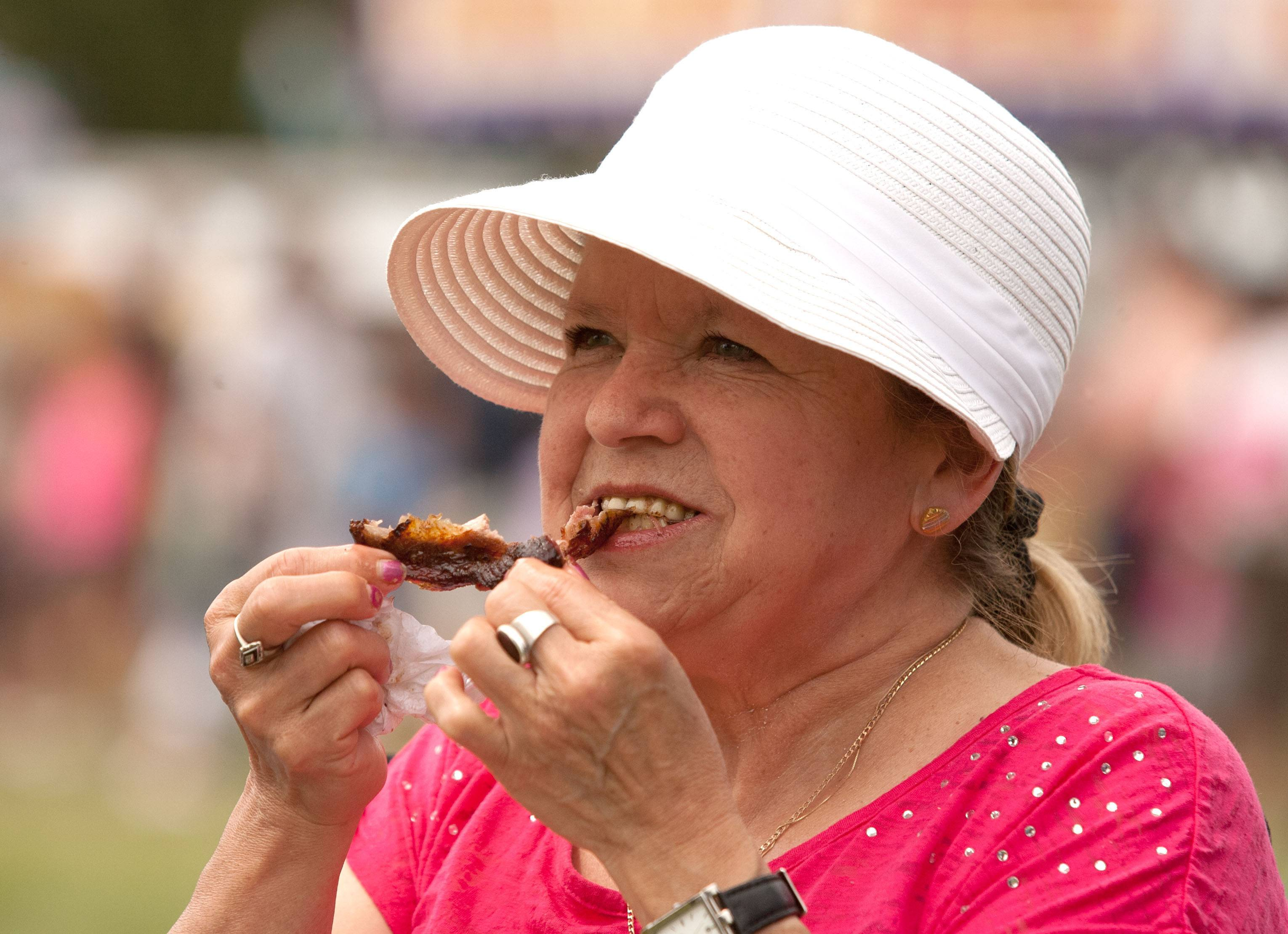 Ofelia Nasir of Burbank eats ribs during the first Hispanic Day at Ribfest in Naperville.