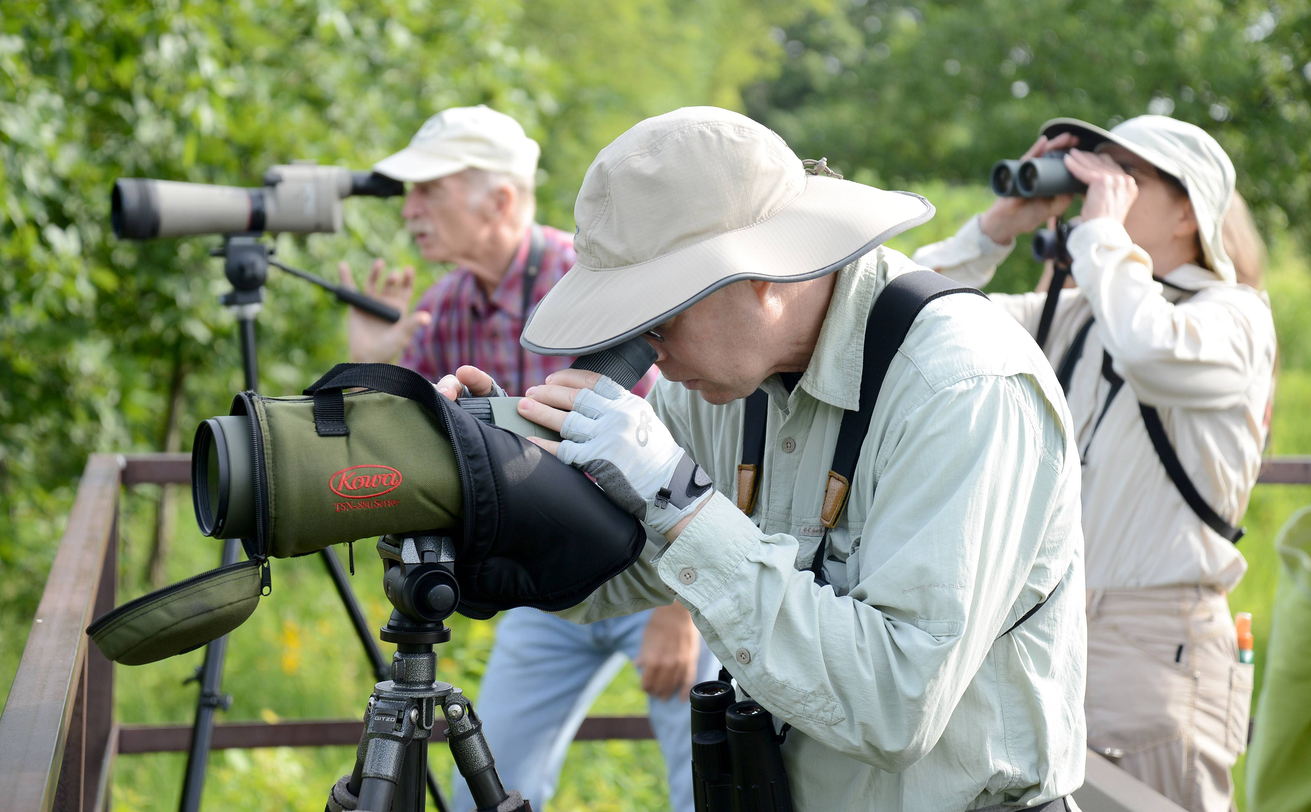 Kane County Audubon Society member Terry Murray of Aurora, center, uses a scope to scan Nelson Lake with Phil Doncheck of Rockford, left, and Theresa LeCompte, right, of Aurora, during a bird walk at Dick Young Forest Preserve in Batavia on Saturday. Murray leads walks on the first Saturday of every month starting at 8 a.m.