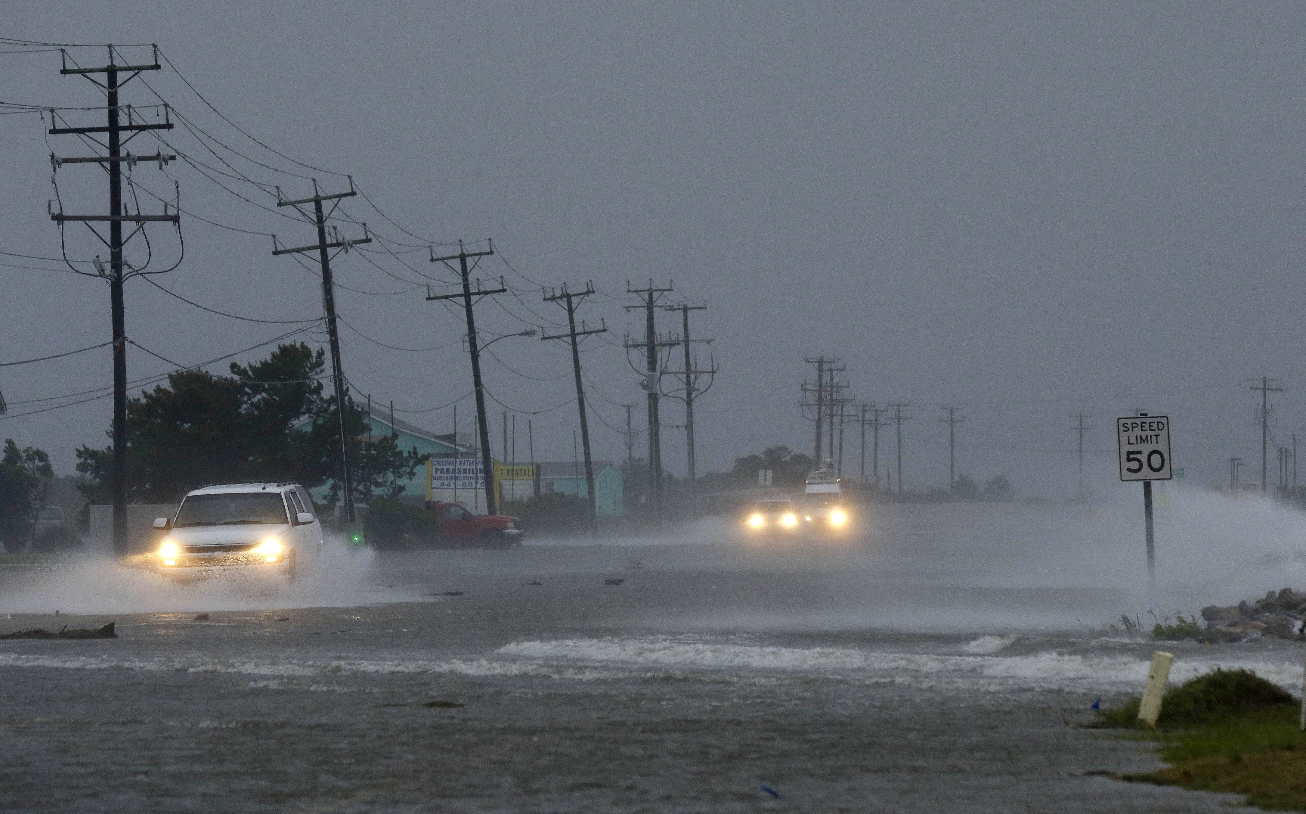 Vehicles navigate a flooded Highway 64 Friday as wind from Hurricane Arthur pushes water over the road anear Nags Head, N.C.,