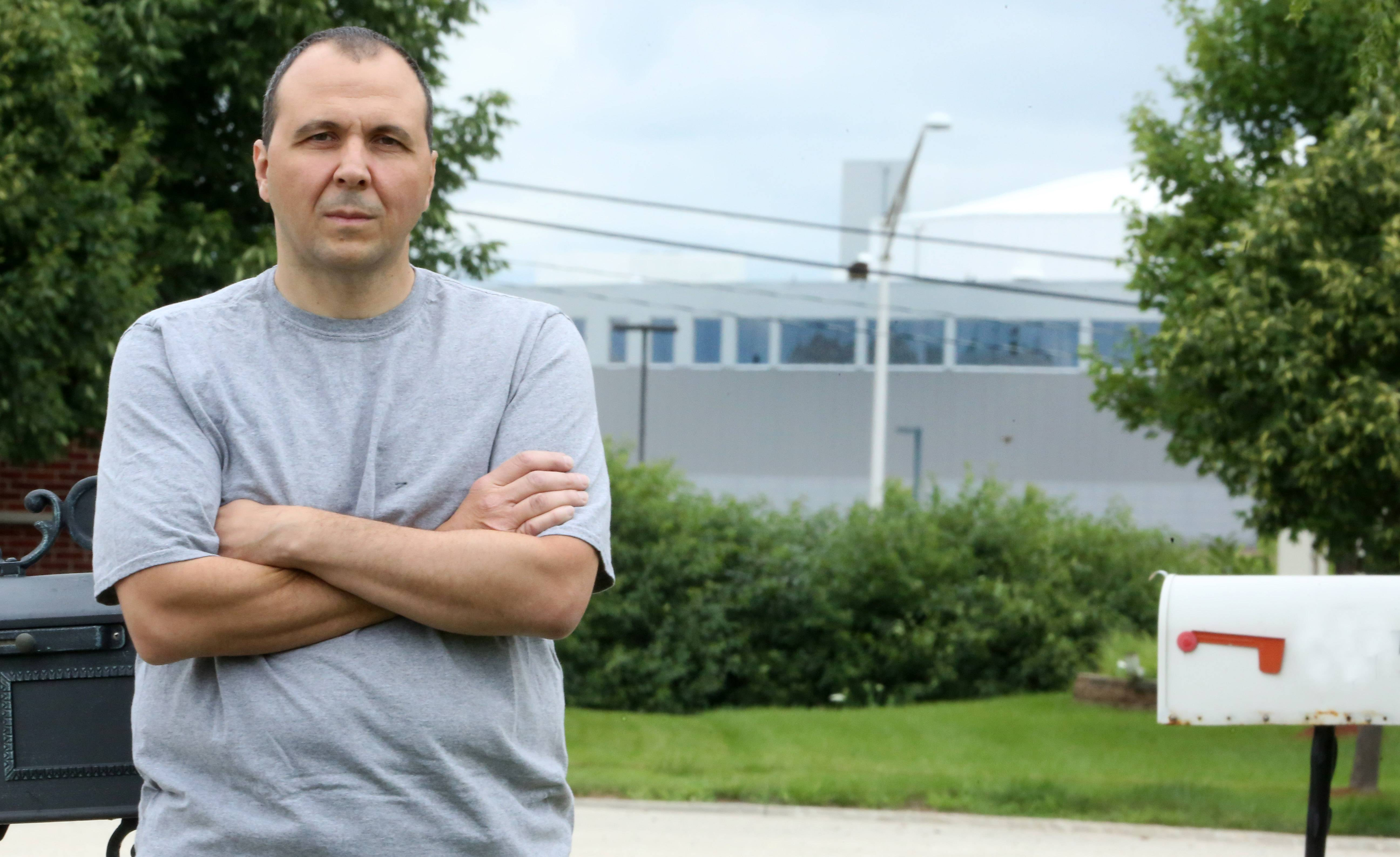 John Manfredi of Hoffman Estates stands next to his home mailbox with the Sears Centre Arena, across the tollway, in the background. Manfredi and his neighbors say long-running car racing events in the Sears Centre parking lot are too noisy.