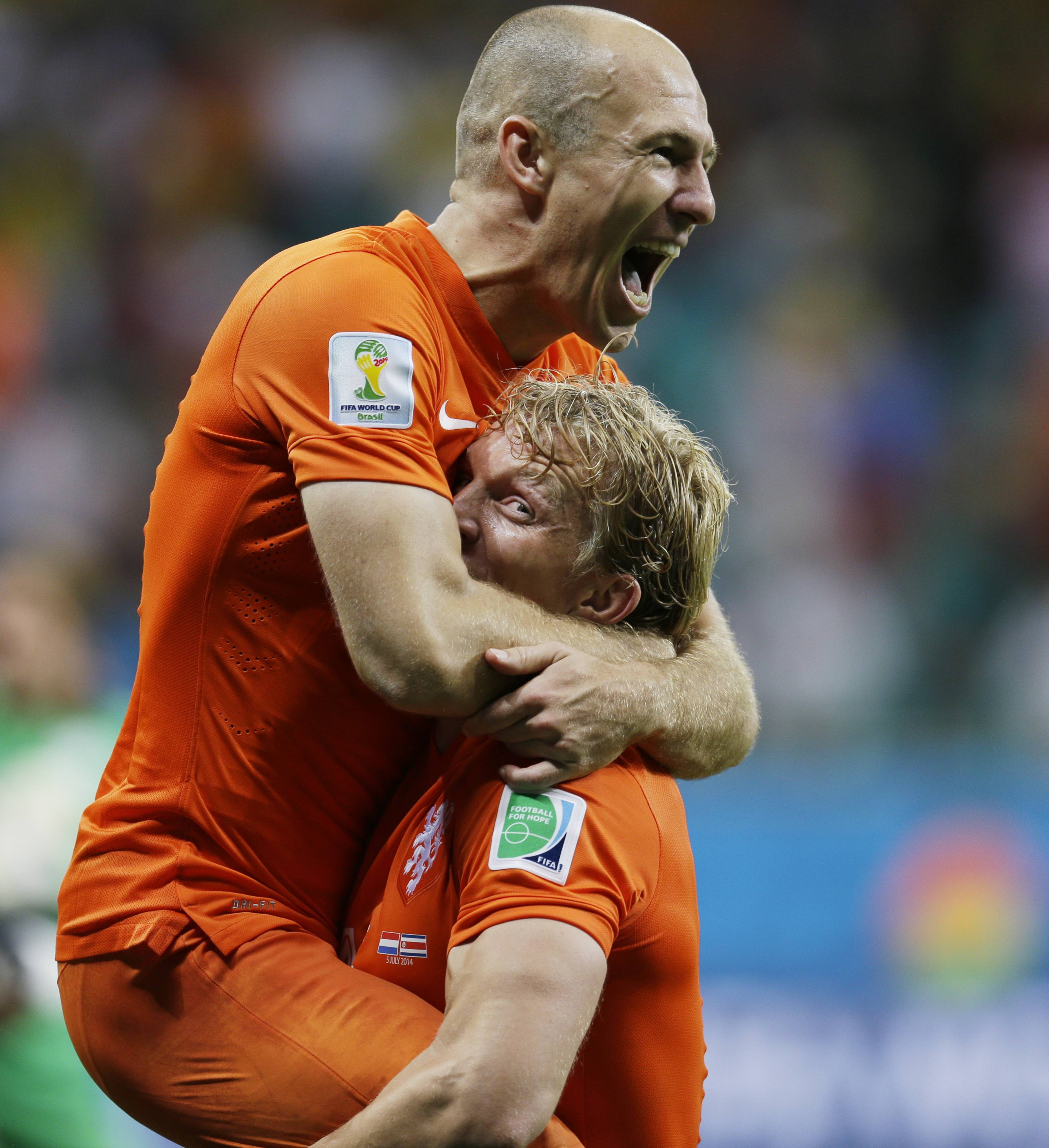 Netherlands' Arjen Robben celebrates with Dirk Kuyt after the Netherlands defeated Costa Rica 4-3 in a penalty shootout after a 0-0 tie during the World Cup quarterfinal soccer match at the Arena Fonte Nova in Salvador, Brazil, Saturday, July 5, 2014.