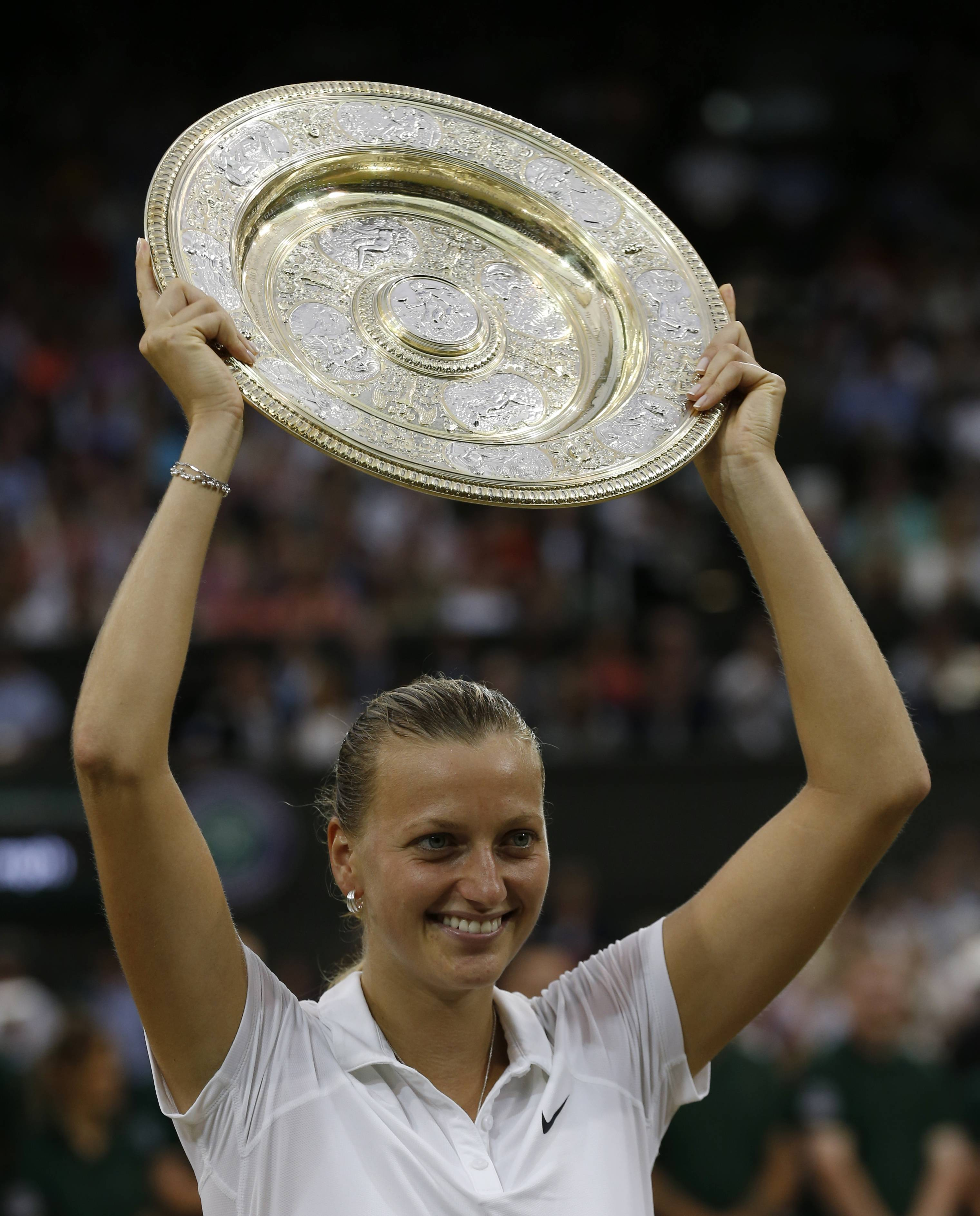 Petra Kvitova of Czech Republic holds up the trophy after winning the women's singles final against Eugenie Bouchard of Canada at the All England Lawn Tennis Championships in Wimbledon, London, Saturday July 5.