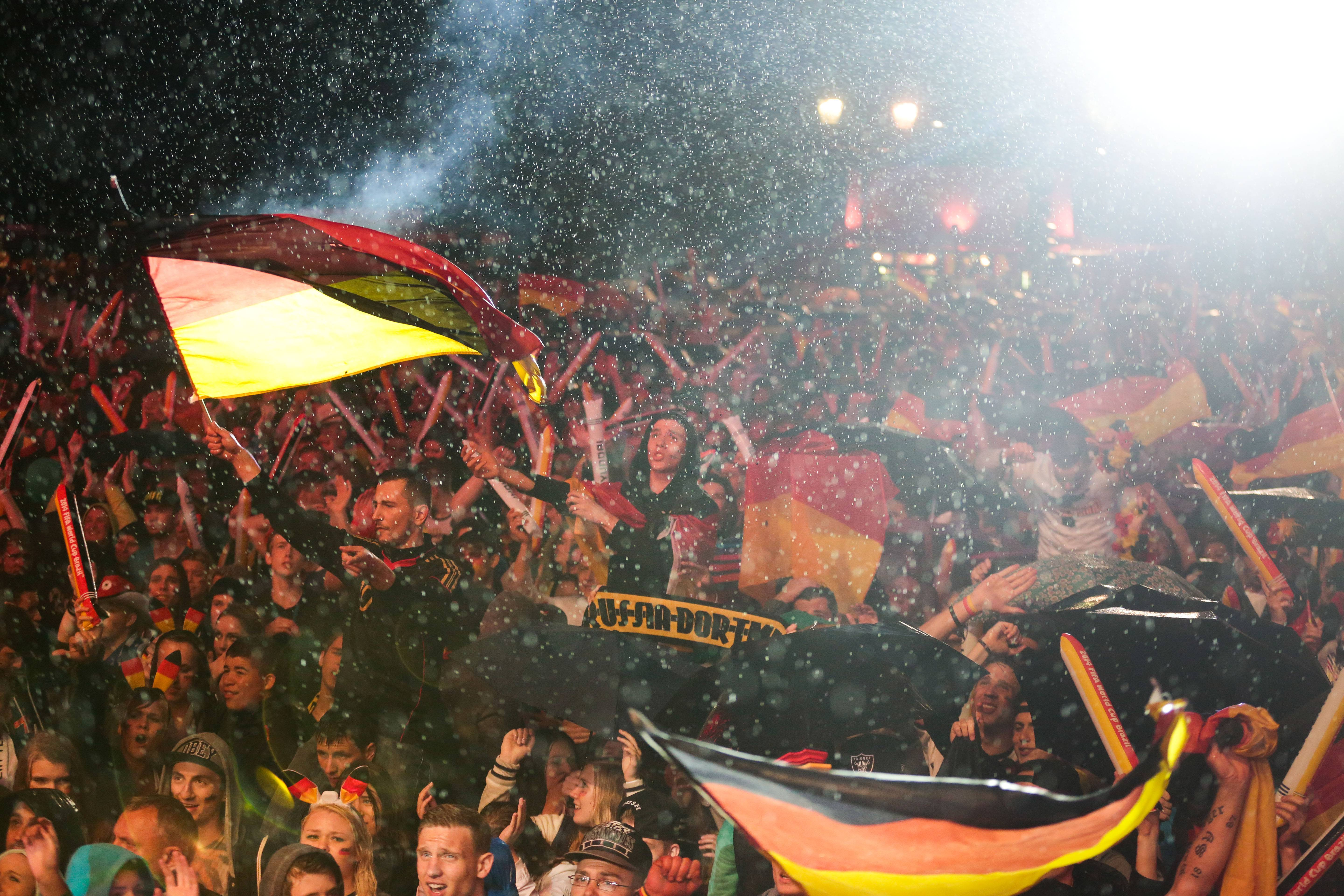German soccer fans celebrate the kick off of the Brazil World Cup round of 16 soccer match between Germany and Algeria during heavy rain at a public viewing event in Berlin, Monday, June 30, 2014.  Germany plays Algeria at the Estadio Beira-Rio in Porto Alegre, Brazil, Monday.