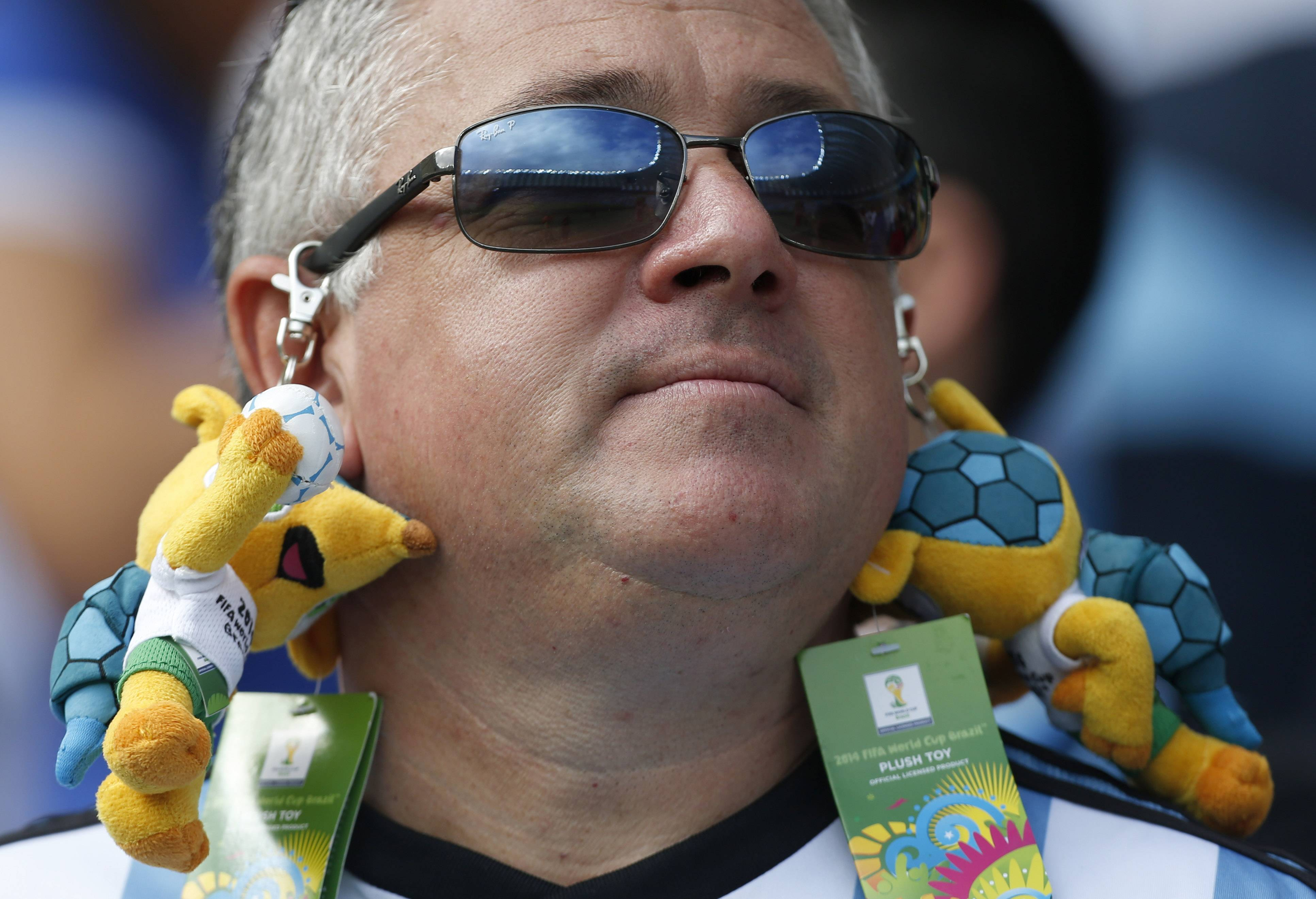 An Argentine supporter has stuffed-toy World Cup mascots attached to his sunglasses before the group F World Cup soccer match between Nigeria and Argentina at the Estadio Beira-Rio in Porto Alegre, Brazil, Wednesday, June 25, 2014.