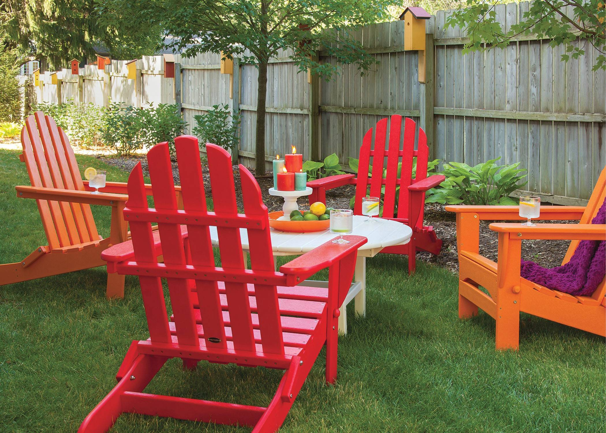 Old school, new style: A conversational grouping of Poly-Wood's classic Adirondack chairs and a woven rocker made from recycled plastic. At the end of its life as seating, the furniture can be recycled and remade into something new.