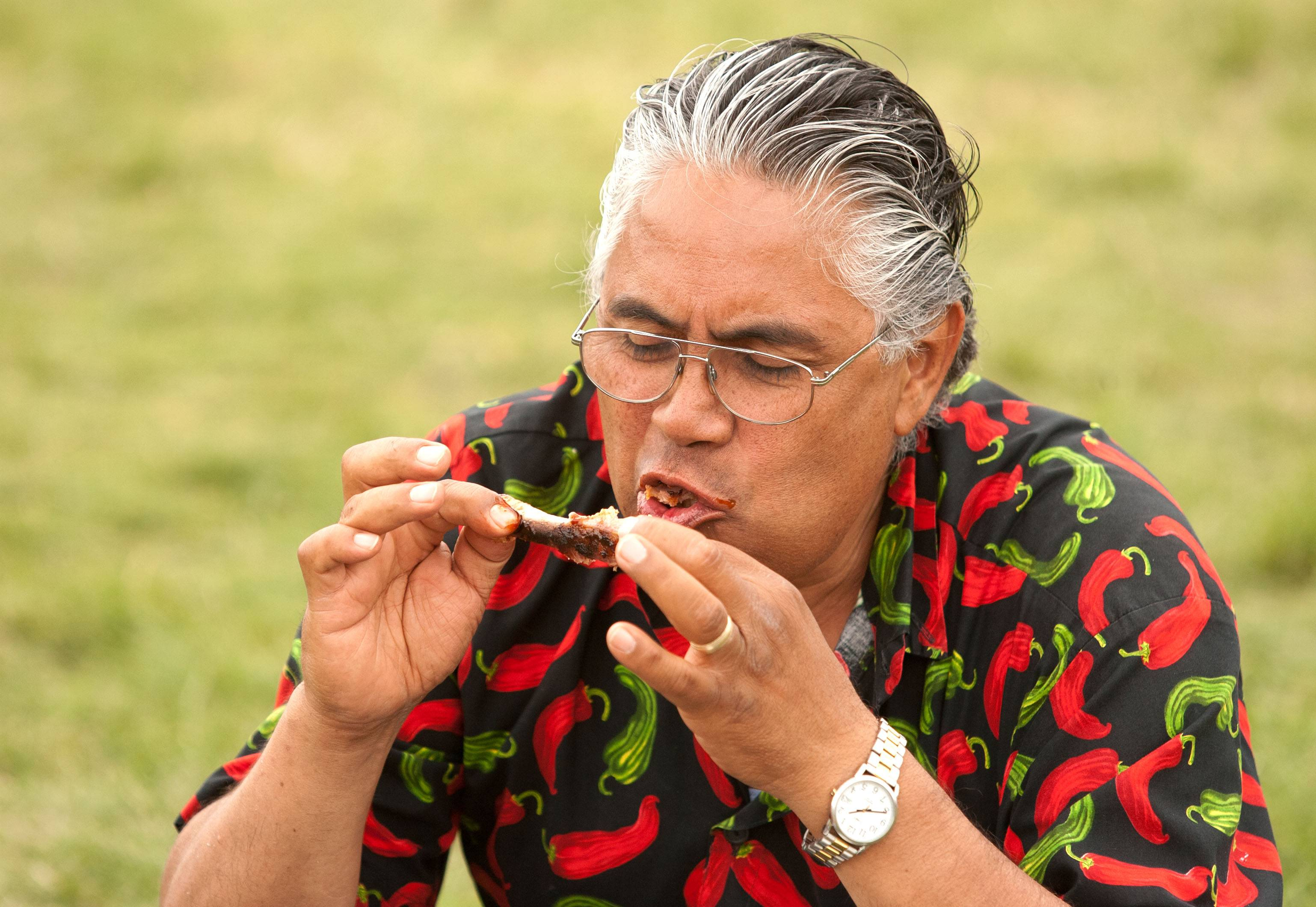 Robert Vasquez of Des Plaines enjoys his ribs during the first Hispanic Day at Ribfest in Naperville.