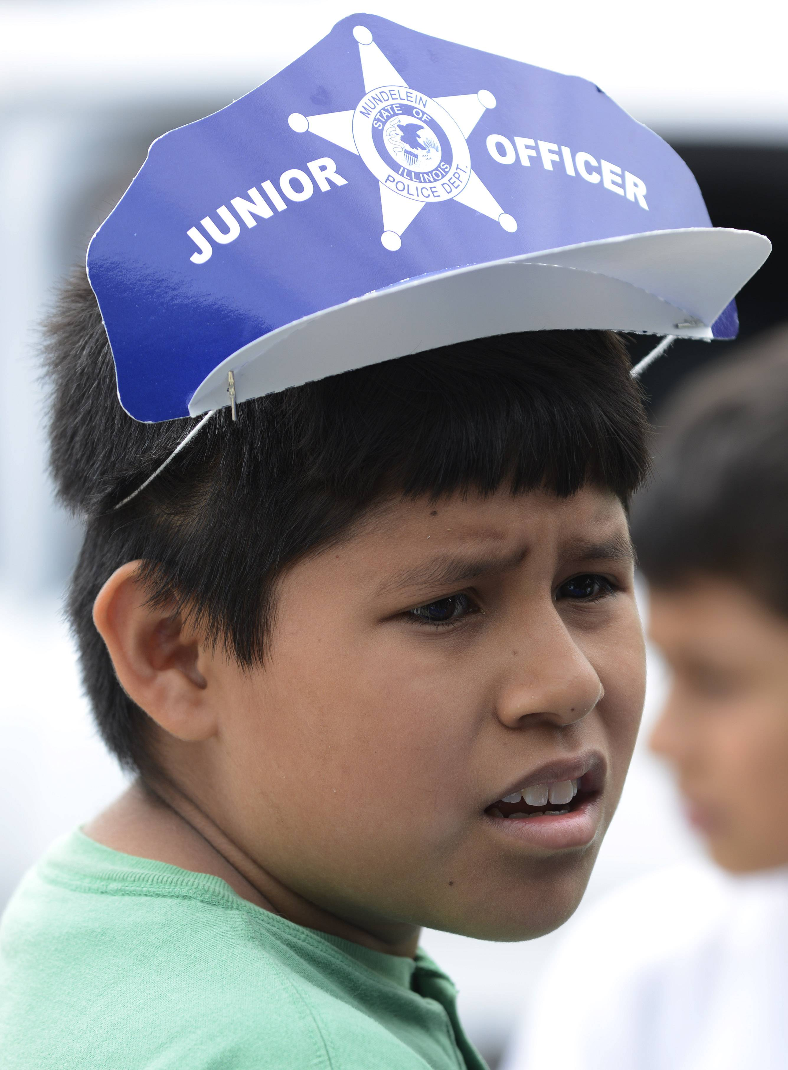 Oswaldo Rosales, 12, of Mundelein wears a cap from the police department Saturday during the third day of Mundelein Community Days.