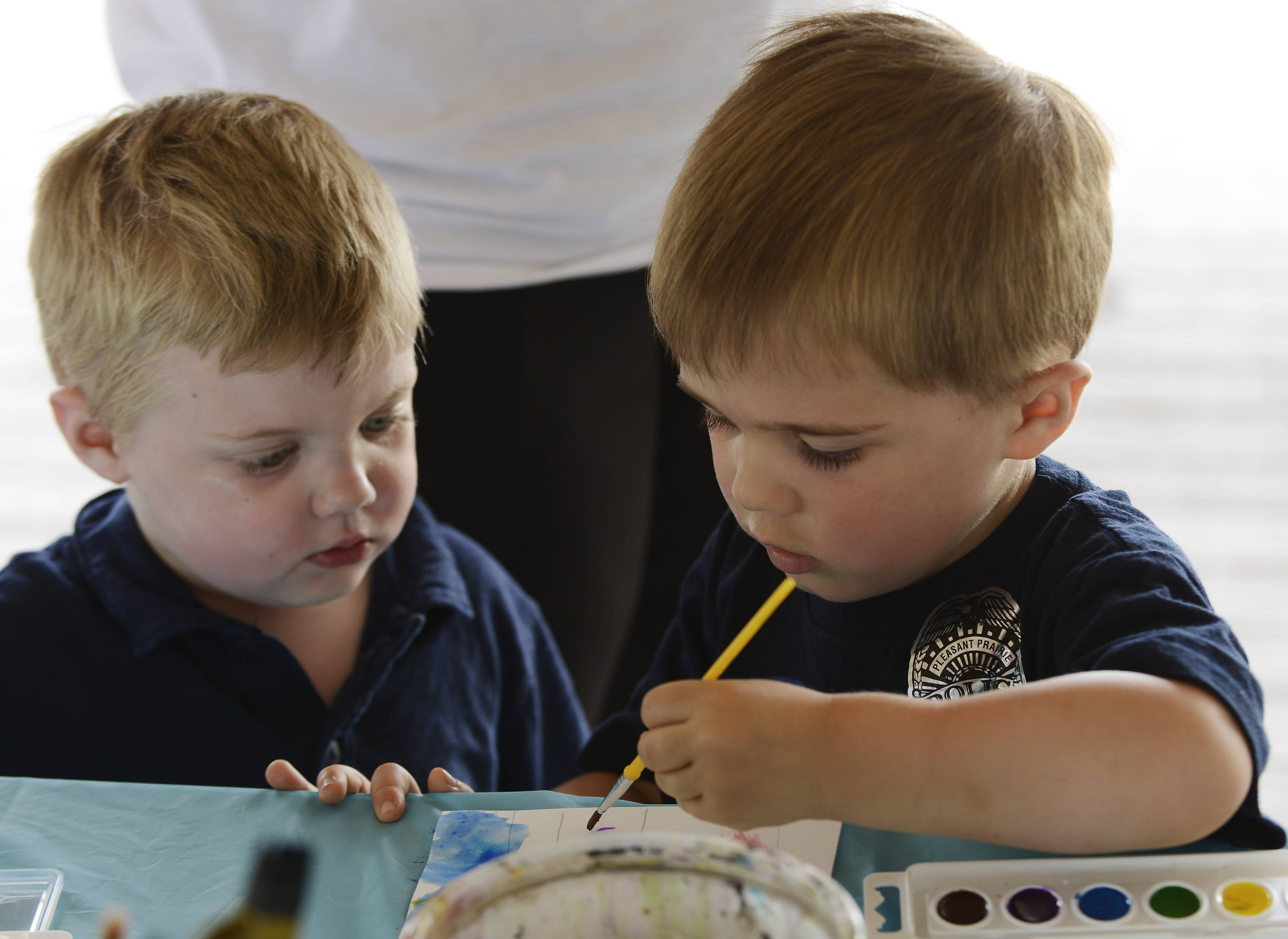 Blake De Tota, 3, left, and Austin Harris, 3, of Pleasant Prairie, Wis., paint with watercolors Saturday during the third day of Mundelein Community Days.