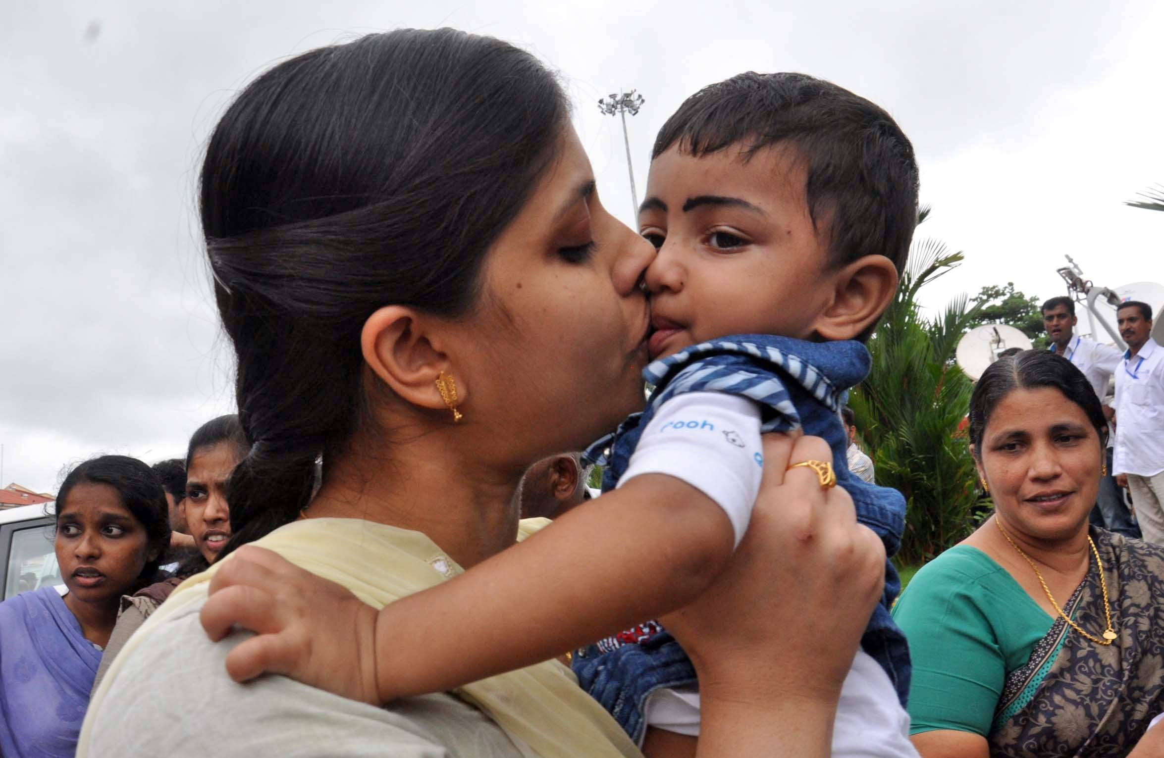 An Indian nurse, who was among 46 nurses stranded in territory held by Islamic extremists in Iraq, kisses her nephew upon arrival at the airport in Kochi, India, Saturday, July 5. The nurses who had been holed up for more than a week in Tikrit, returned home to southern India on Saturday aboard a special flight, officials said.