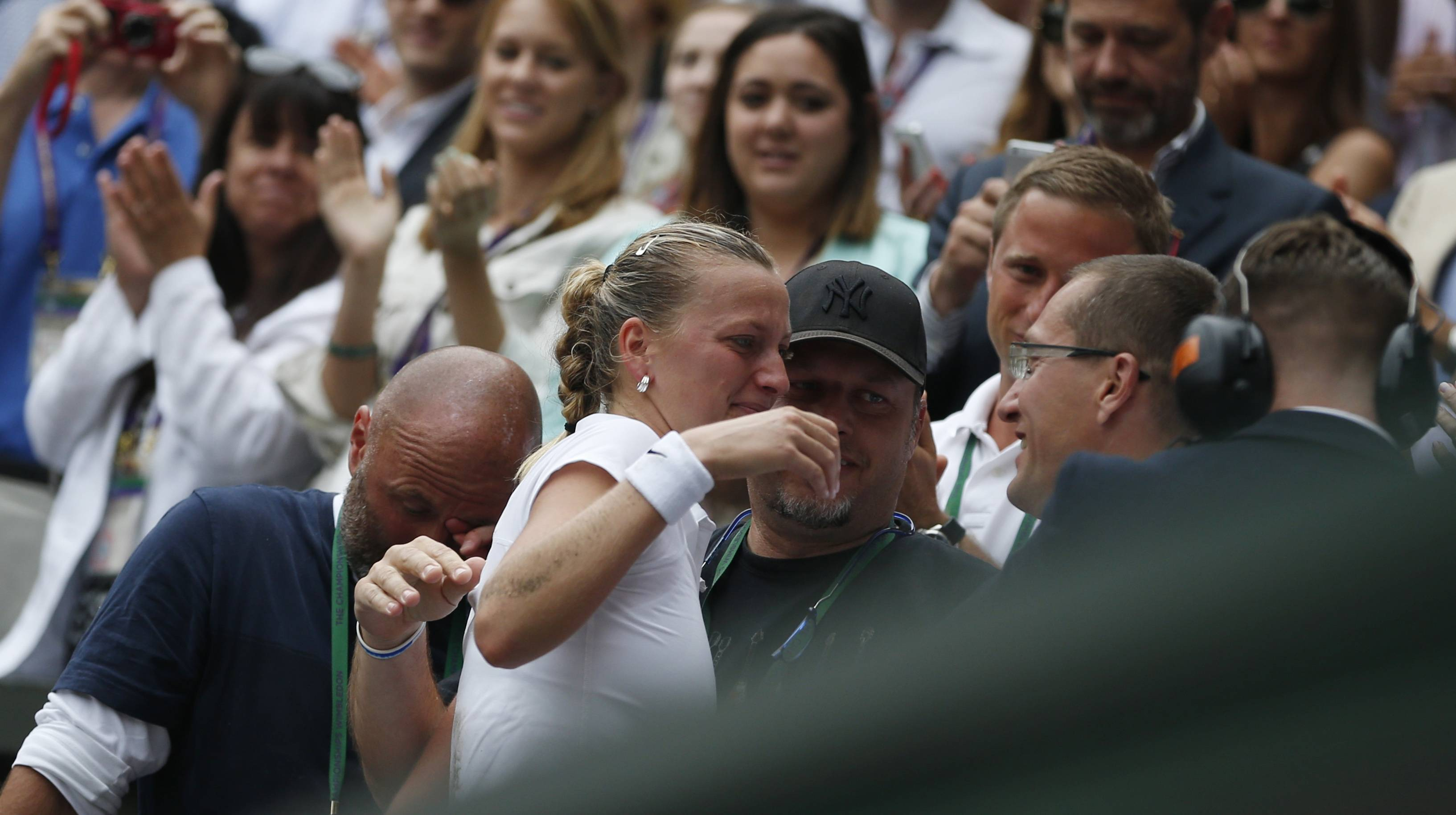 Petra Kvitova of Czech Republic embraces her family and friends in her players box as she celebrates defeating Eugenie Bouchard of Canada in their women's singles final at the All England Lawn Tennis Championships in Wimbledon, London, Saturday July 5.
