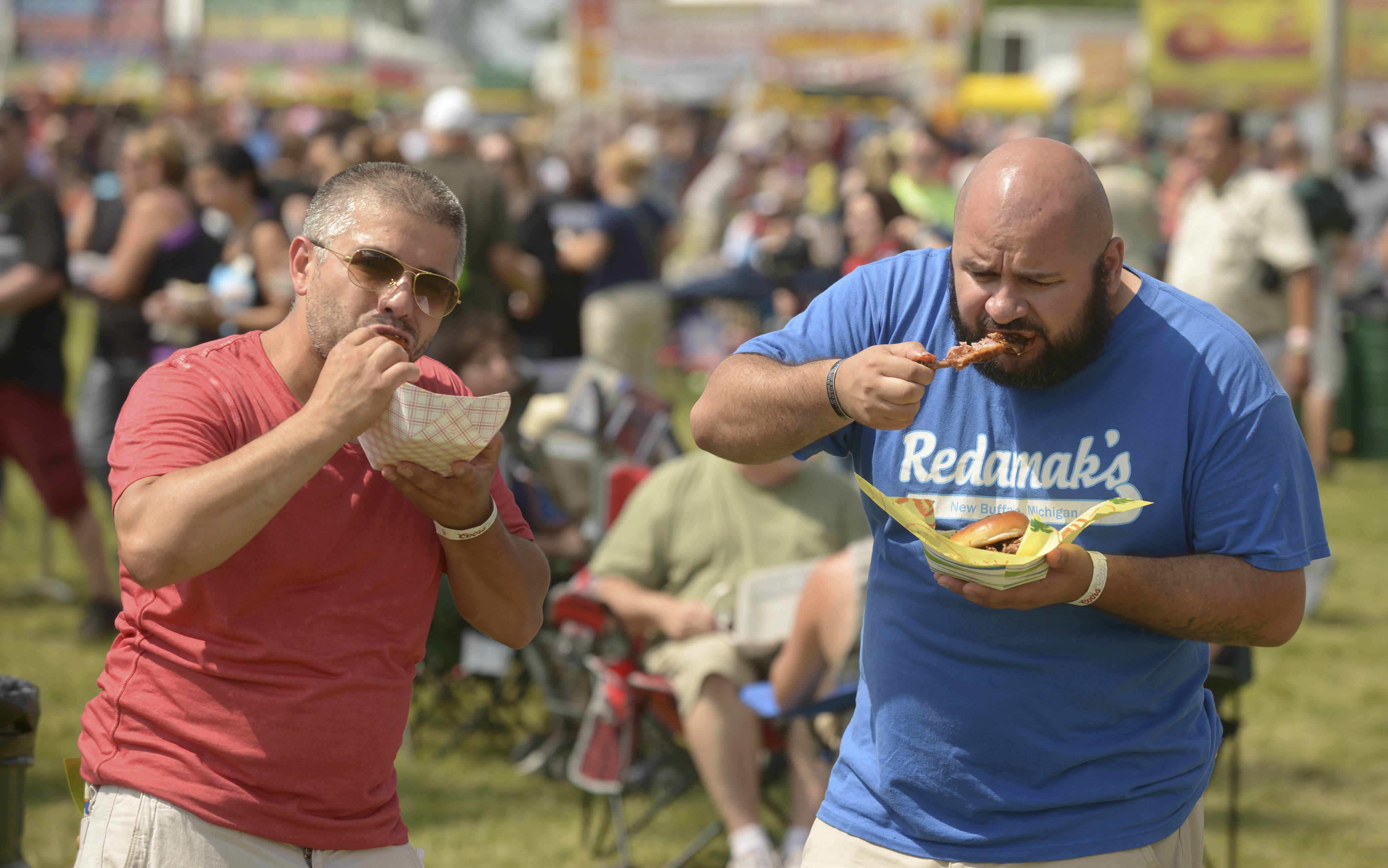 "Jaime Guzman and Joel Arriaga eat some ribs during the final day of the 27th annual Ribfest in Naperville. ""We are going to try them all,"" Guzman said of the dozen rib vendors at the festival."