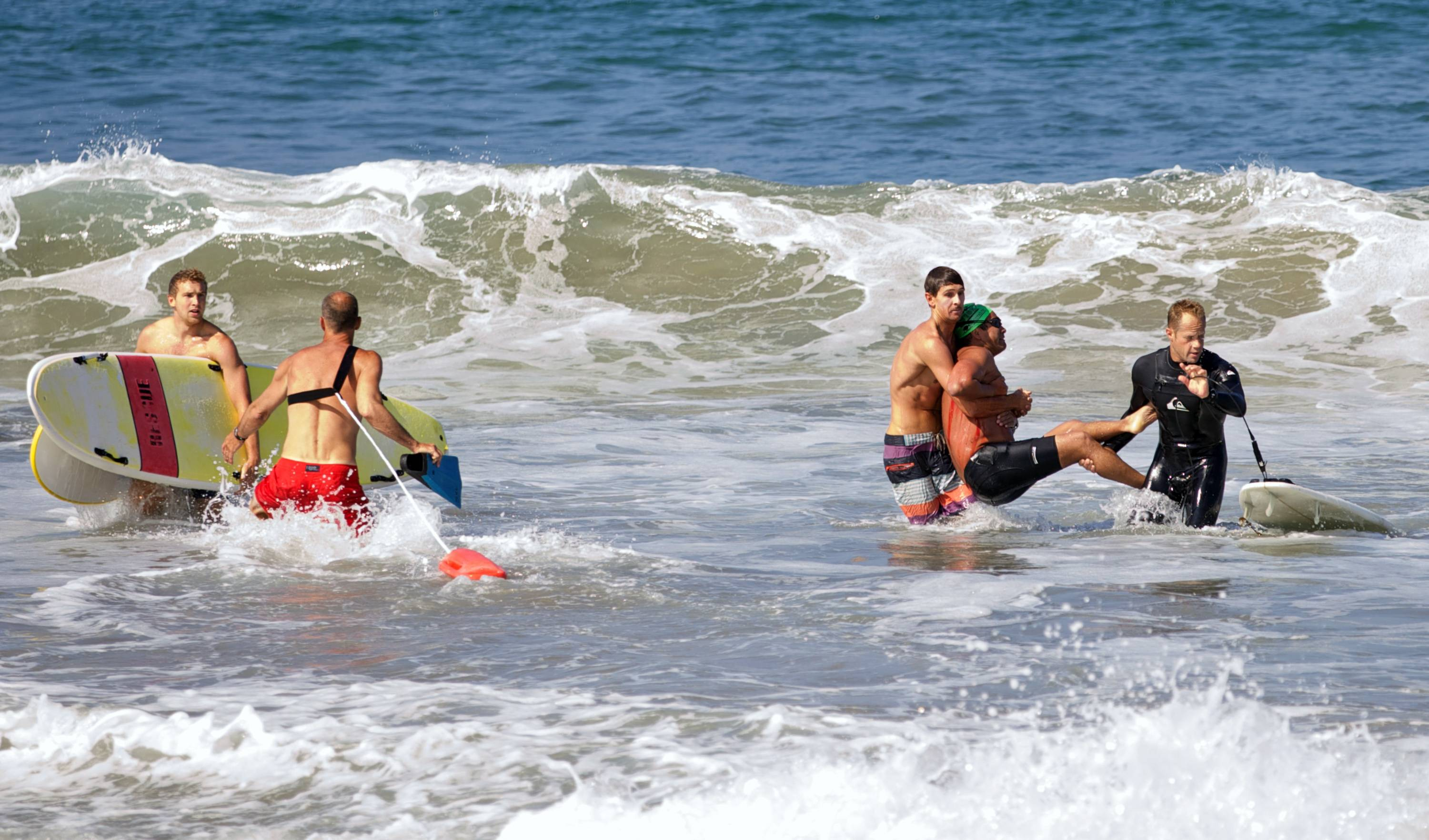 Two men carry a swimmer, second from right, after he was bitten by a great white shark Saturday, as lifeguards close in at left in the ocean off Southern California's Manhattan Beach. The man, who was with a group of long-distance swimmers when he swam into a fishing line, was bitten on a side of his rib cage according to Rick Flores, a Los Angeles County Fire Department spokesman. The man's injuries were not life-threatening and he was taken to a hospital conscious and breathing on his own, Flores said.