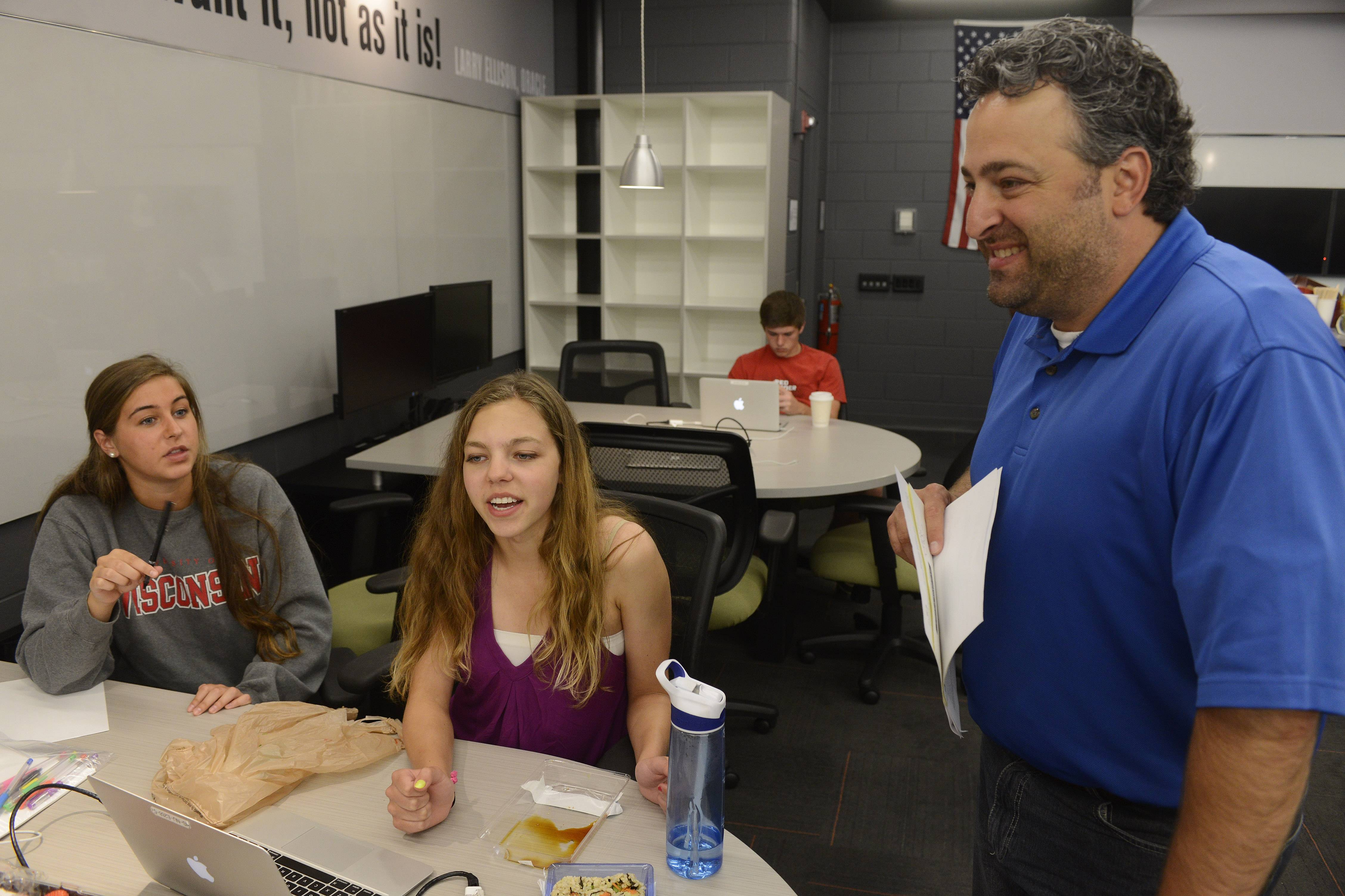 Students Rachel Morin, left, and Sarah Parsons talk about their company, The Study Project, with teacher Hagop Soulakian during a gathering of the Business Incubator class at Barrington High School. The Study Project aims to provide an online meeting place for students to collaborate on school work.