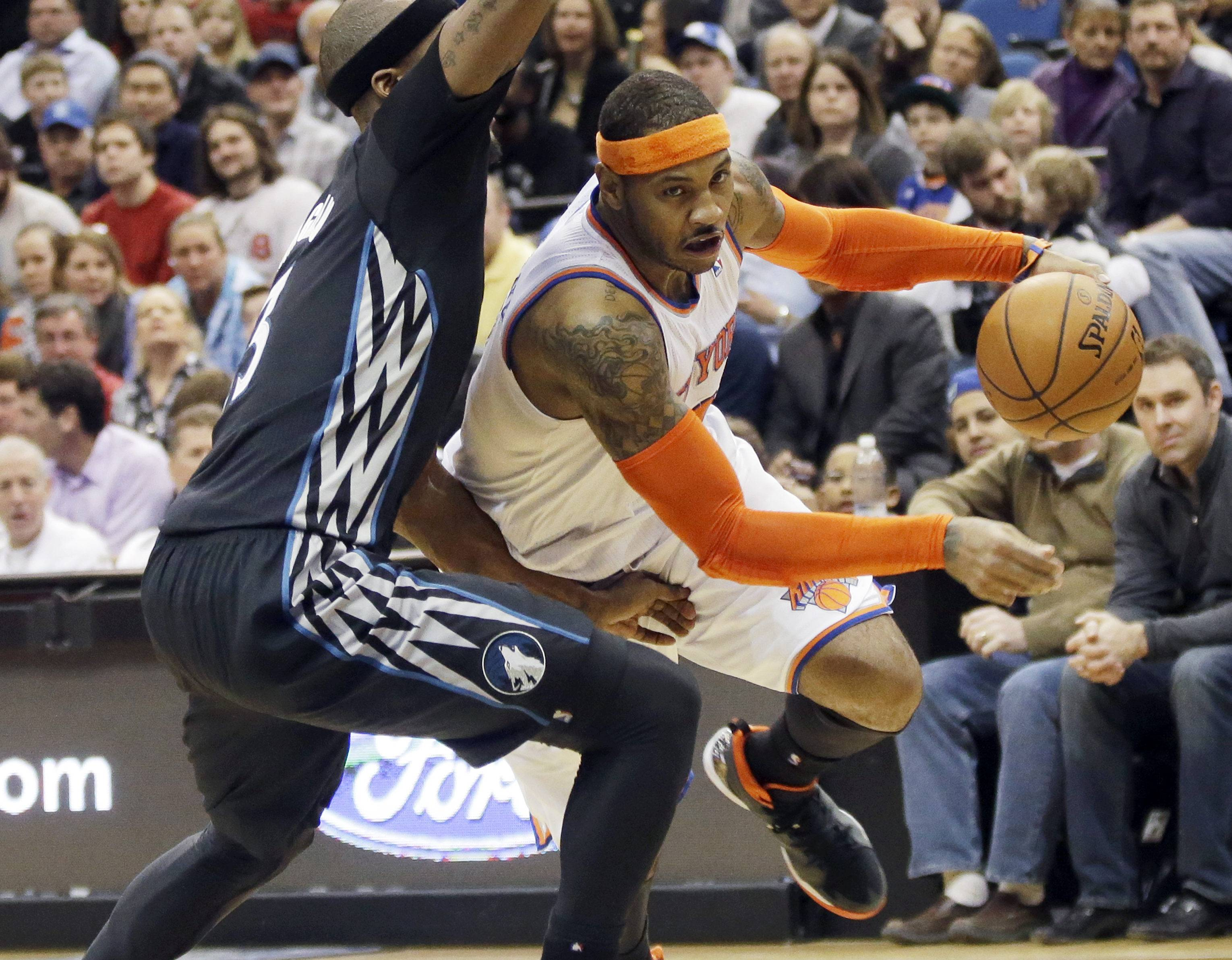In this March 5, 2014, file photo, New York Knicks' Carmelo Anthony, right, leaves the floor as he drives around Minnesota Timberwolves' Dante Cunningham in the second half of an NBA basketball game in Minneapolis. The wait continues on Anthony's decision. Though some say we could find out Monday if he'll be a Bull.