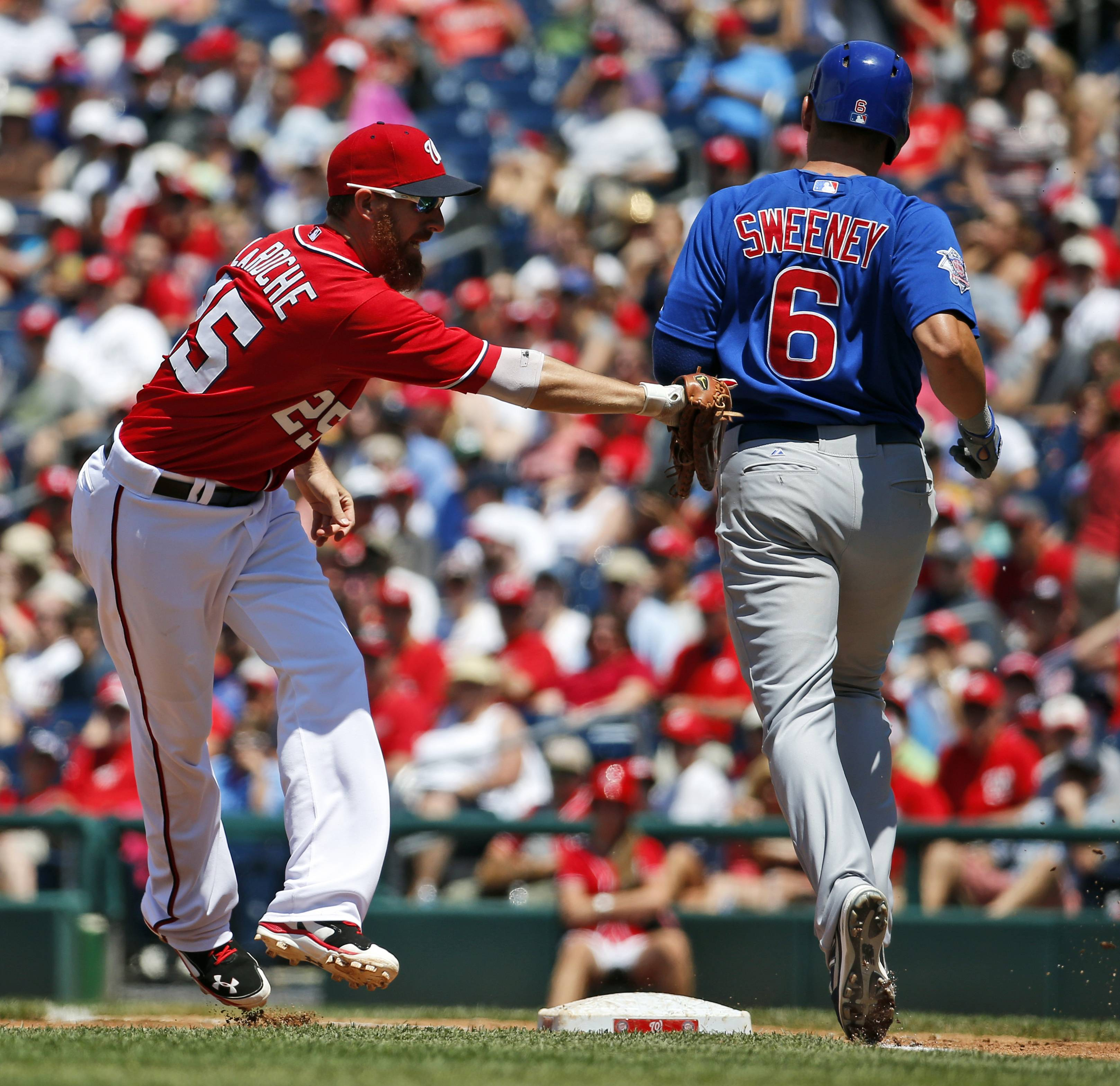 Washington Nationals first baseman Adam LaRoche, left, tags Chicago Cubs' Ryan Sweeney, right, out at first base during the third inning of a baseball game at Nationals Park, Sunday, July 6, 2014, in Washington. Sweeny was called safe, but the play was overturned and he ruled out.