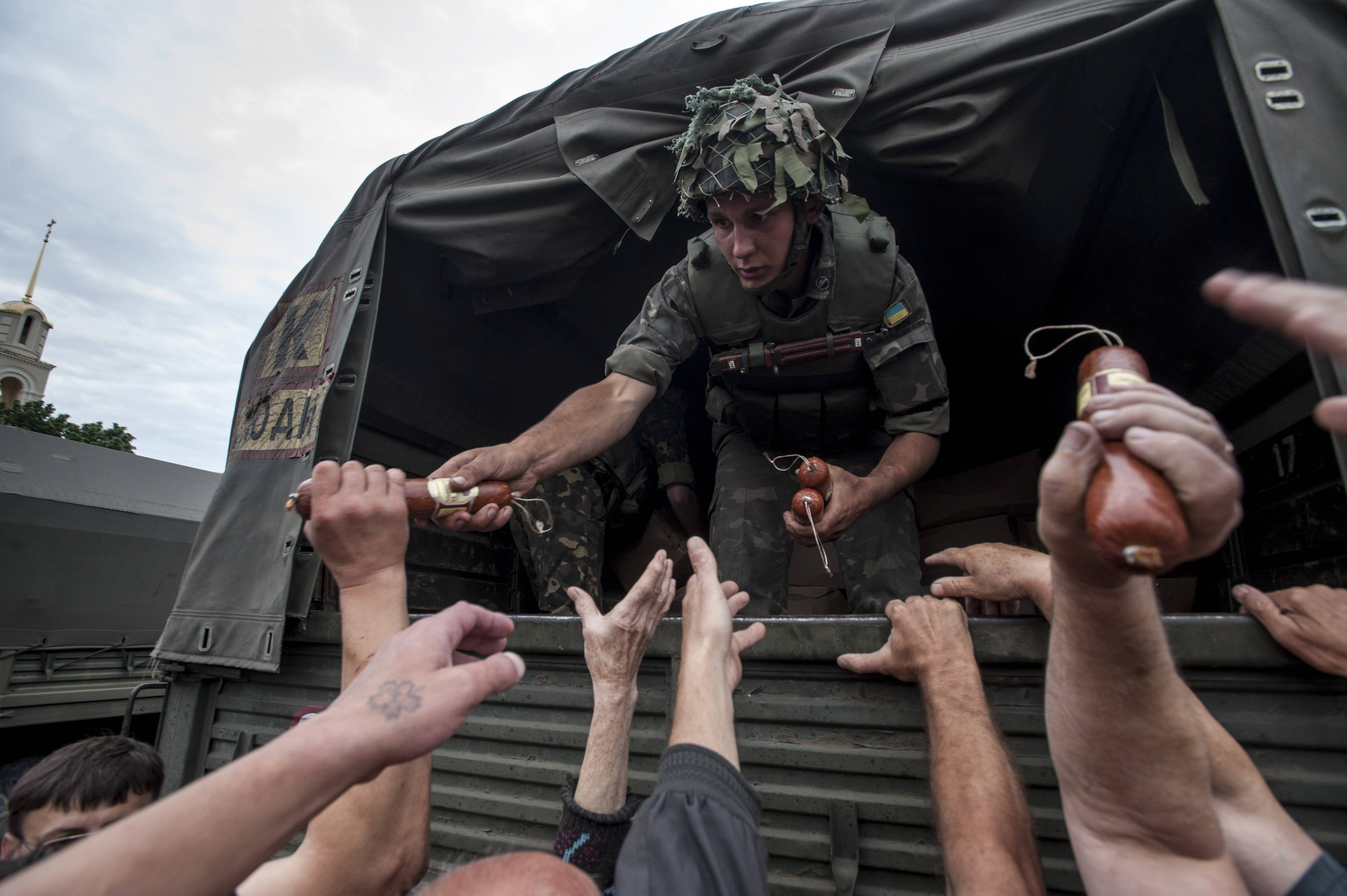 A Ukrainian soldier gives out sausages in Slovyansk, eastern Ukraine, Sunday, a day after Ukrainian troops forced the rebels out of the city that had been the center of the fighting. The success there suggests that the government may finally be making gains in the months-long battle against the insurgency.