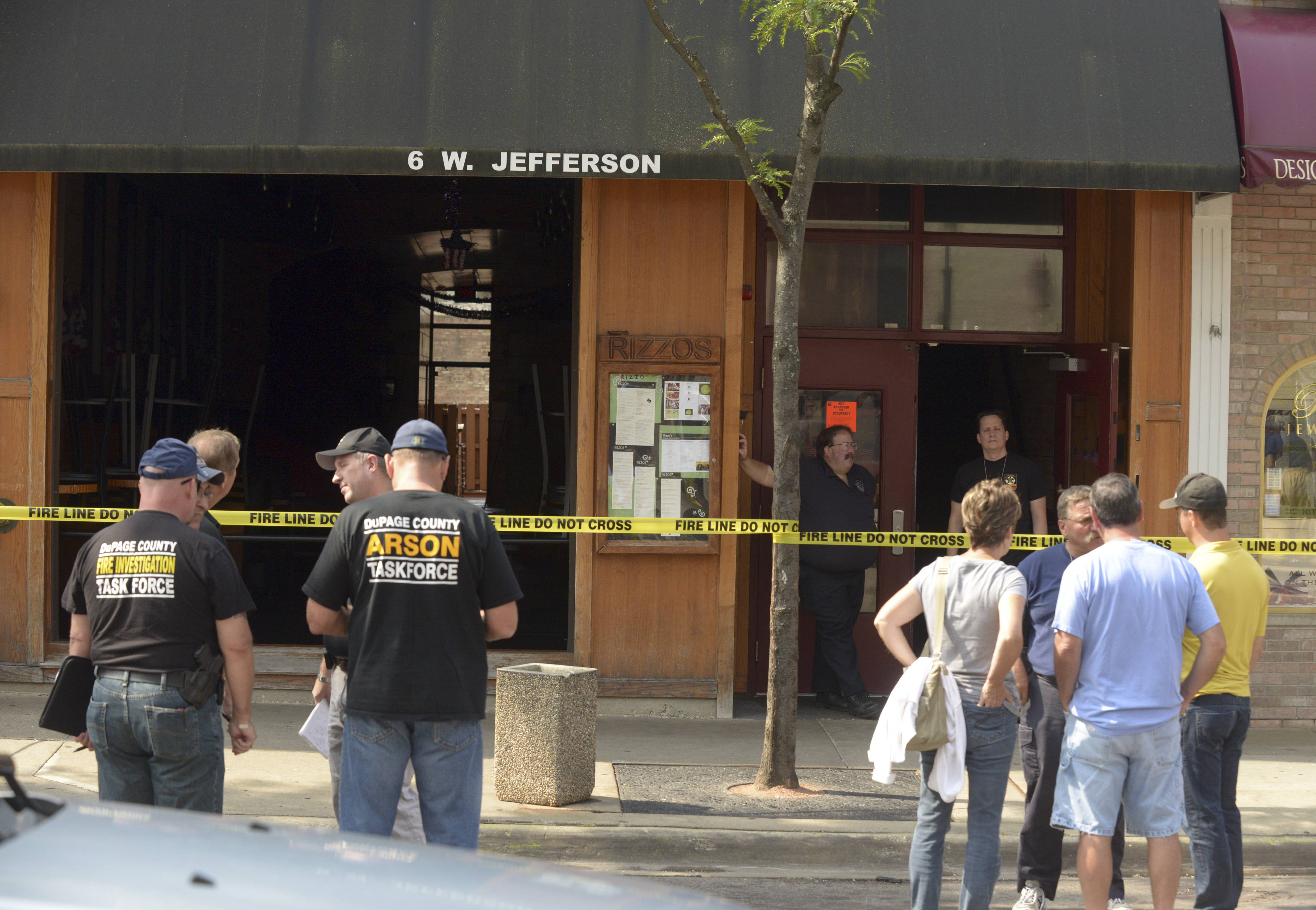 Investigators look over the scene of a fire Sunday morning that caused extensive damage to a restaurant at 6 W. Jefferson Ave. in downtown Naperville. The fire left the business uninhabitable, authorities said.
