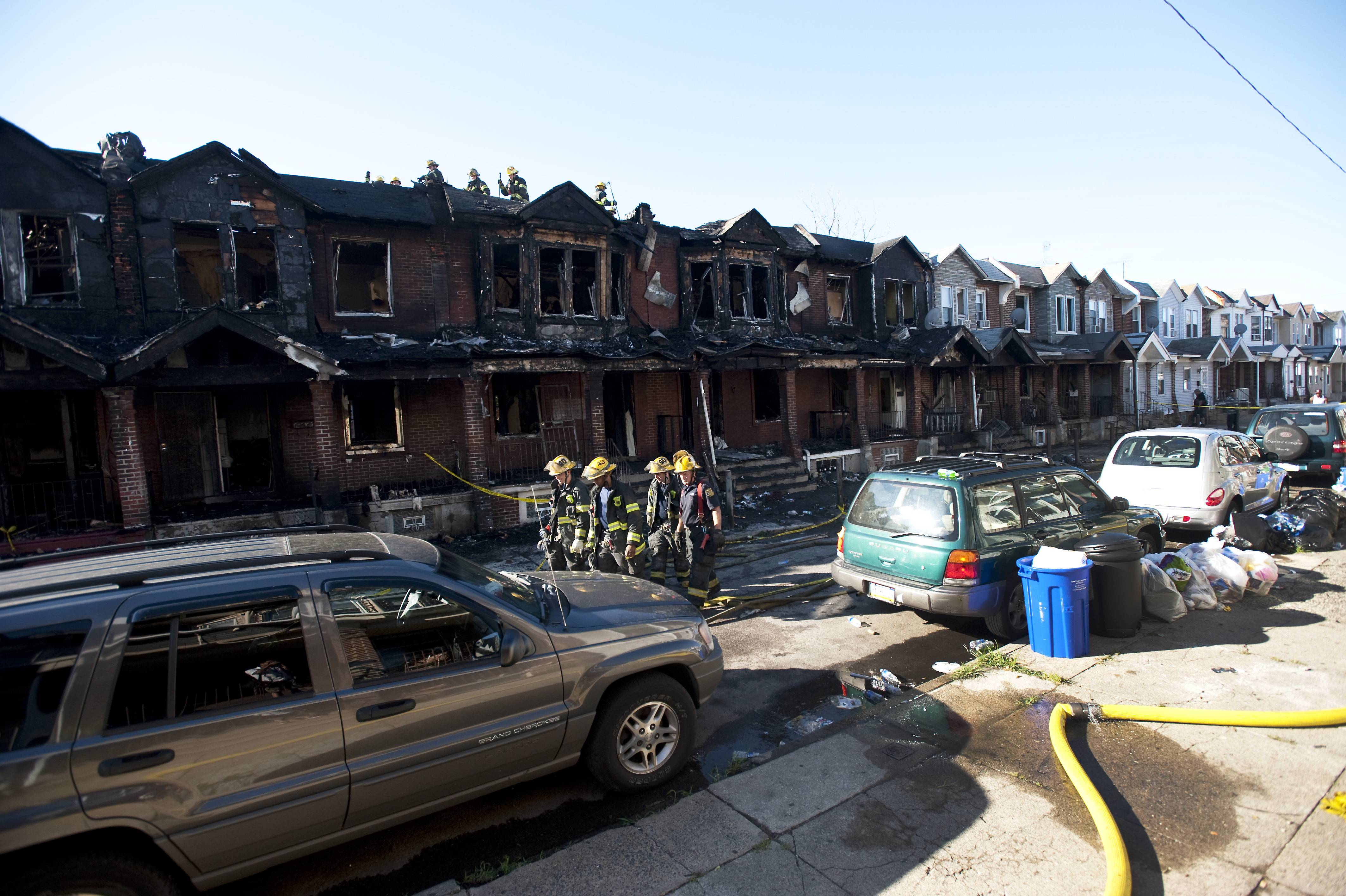 Philadelphia firefighters walk past burned row homes on Saturday in Philadelphia after a fast-moving row house fire early Saturday left four children dead. Fire department officials say there is no immediate word on how many others were injured in the blaze that destroyed eight homes in the row and engulfed a total of 10 houses.