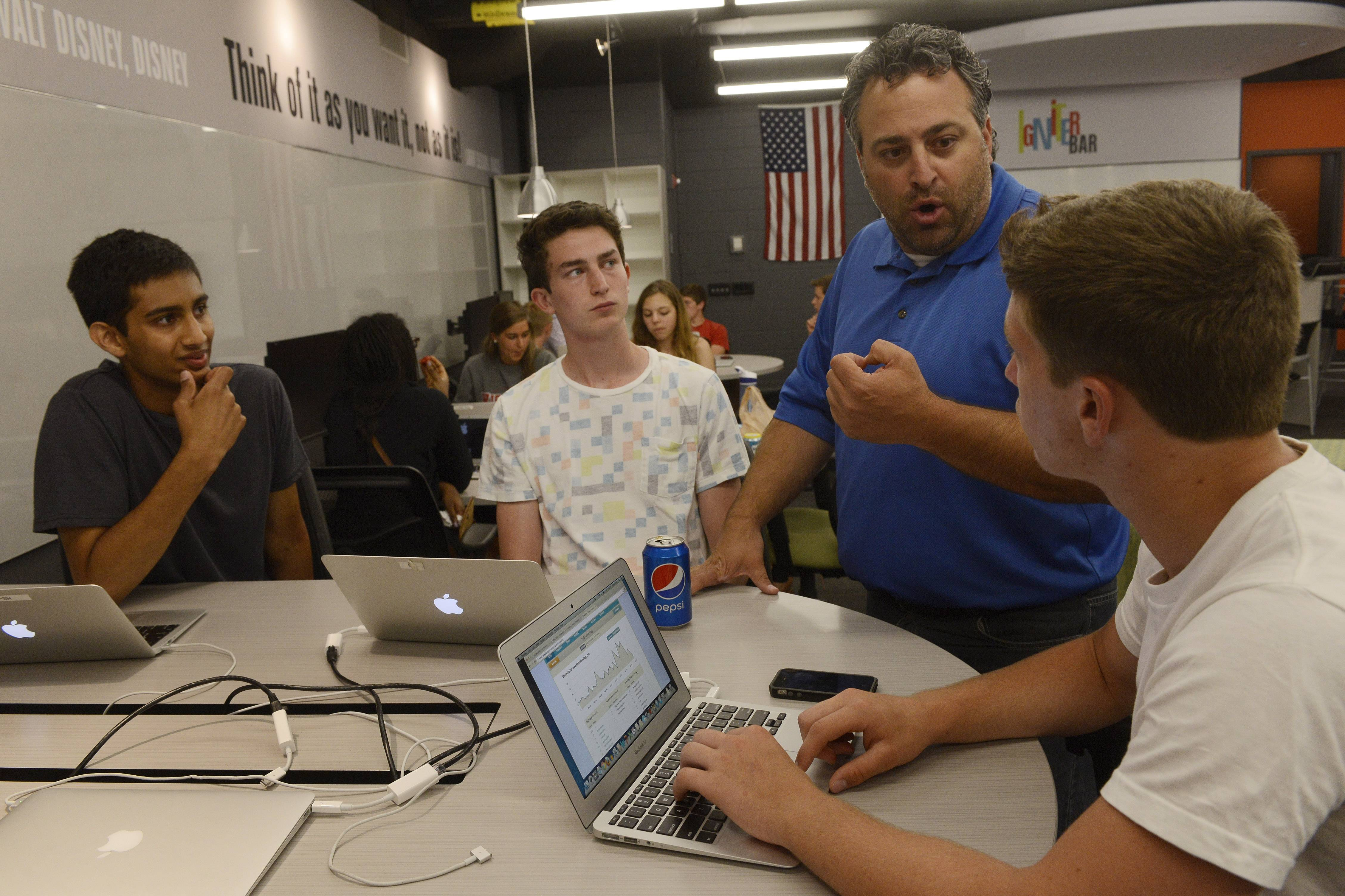 From left, Sanjit Narendra, Jack Lenihan and Connor Boundy talk with teacher Hagop Soulakian during a gathering of the Business Incubator class at Barrington High School.