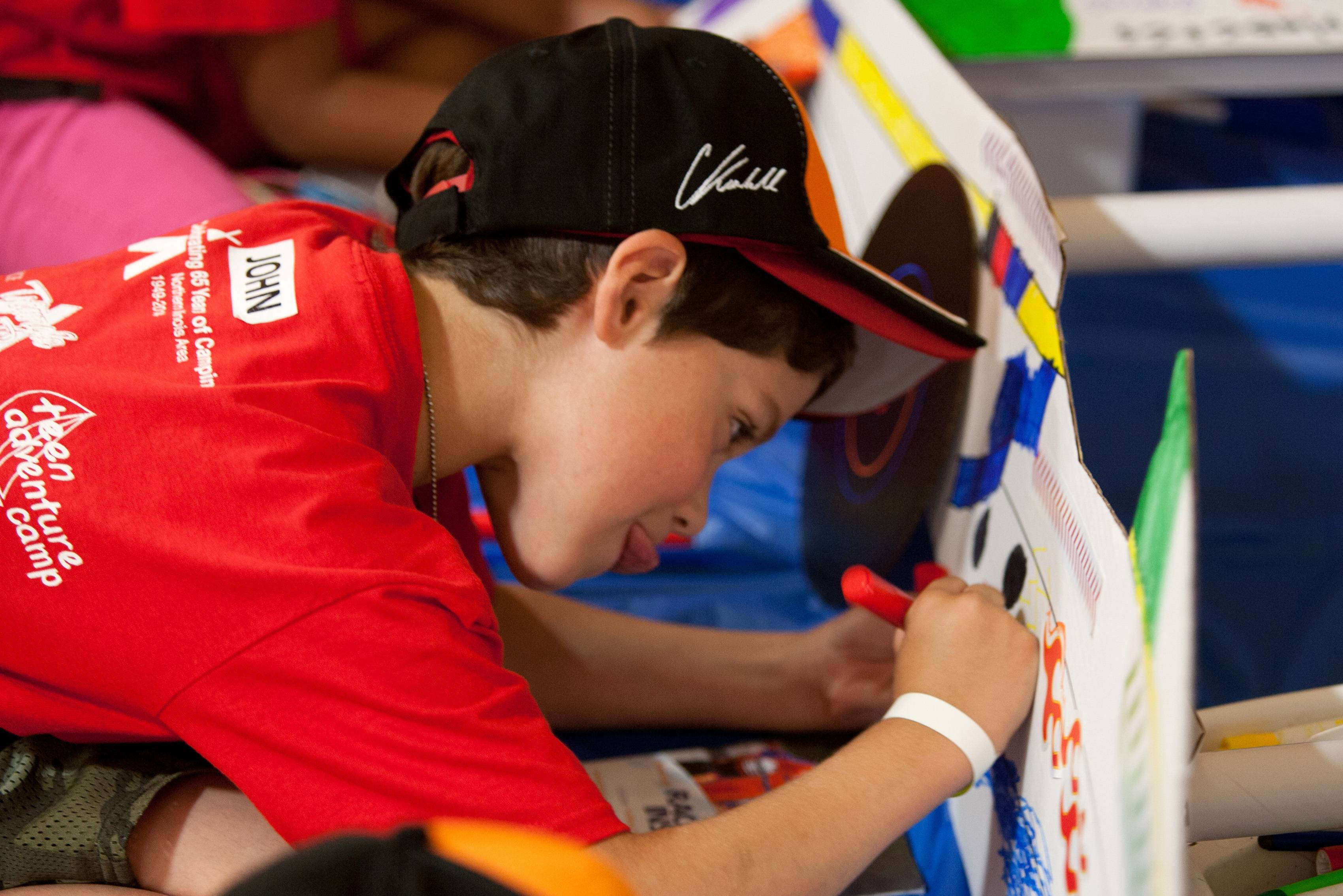 John Beaudette, 7, works on coloring a cardboard model of Charlie Kimball's 83 Indy car.