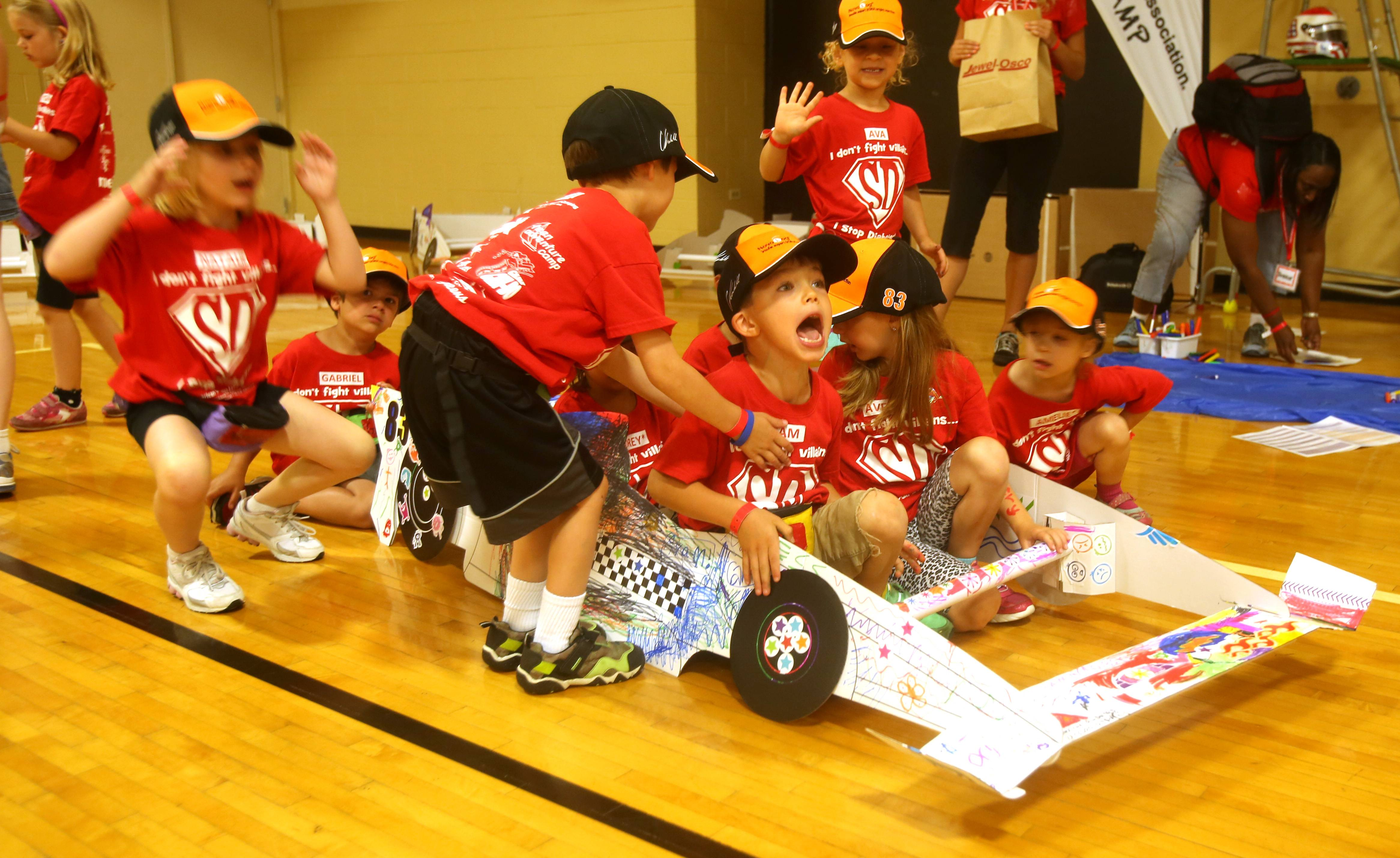 With their decorating work done, the kids try out their Indy car with Sam Modjeski yelling for the car to move.