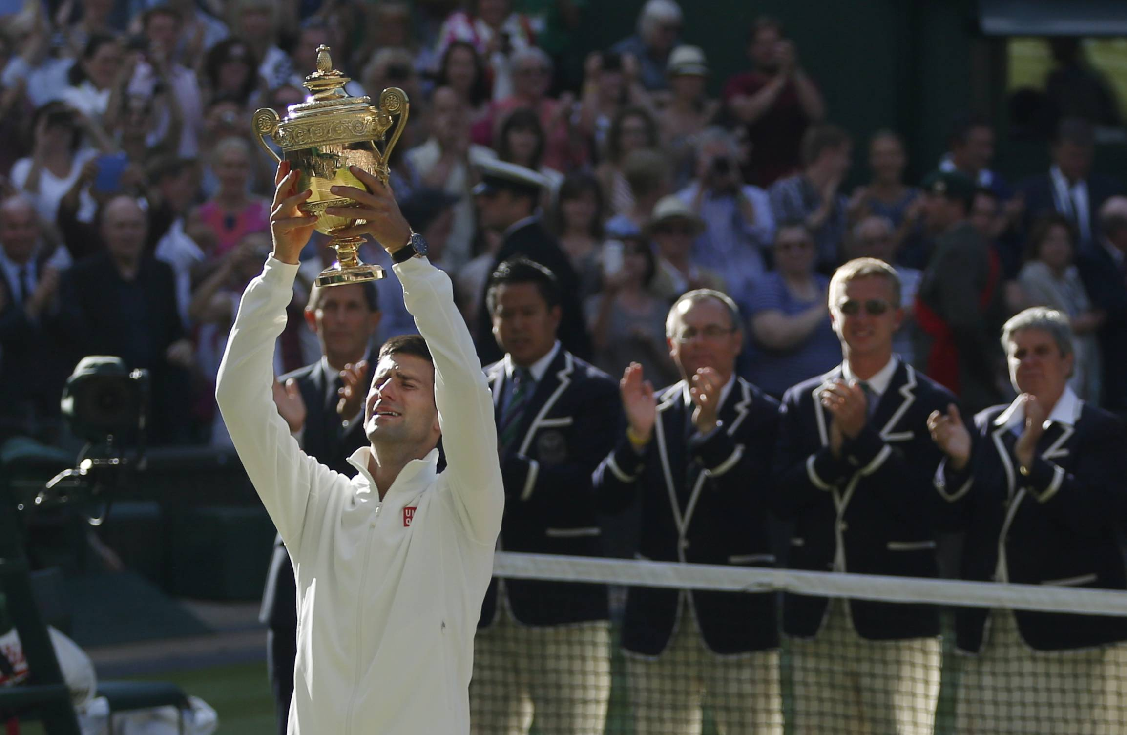 Novak Djokovic of Serbia holds the trophy after defeating Roger Federer of Switzerland in the men's singles final at the All England Lawn Tennis Championships in Wimbledon, London, Sunday July 6, 2014.