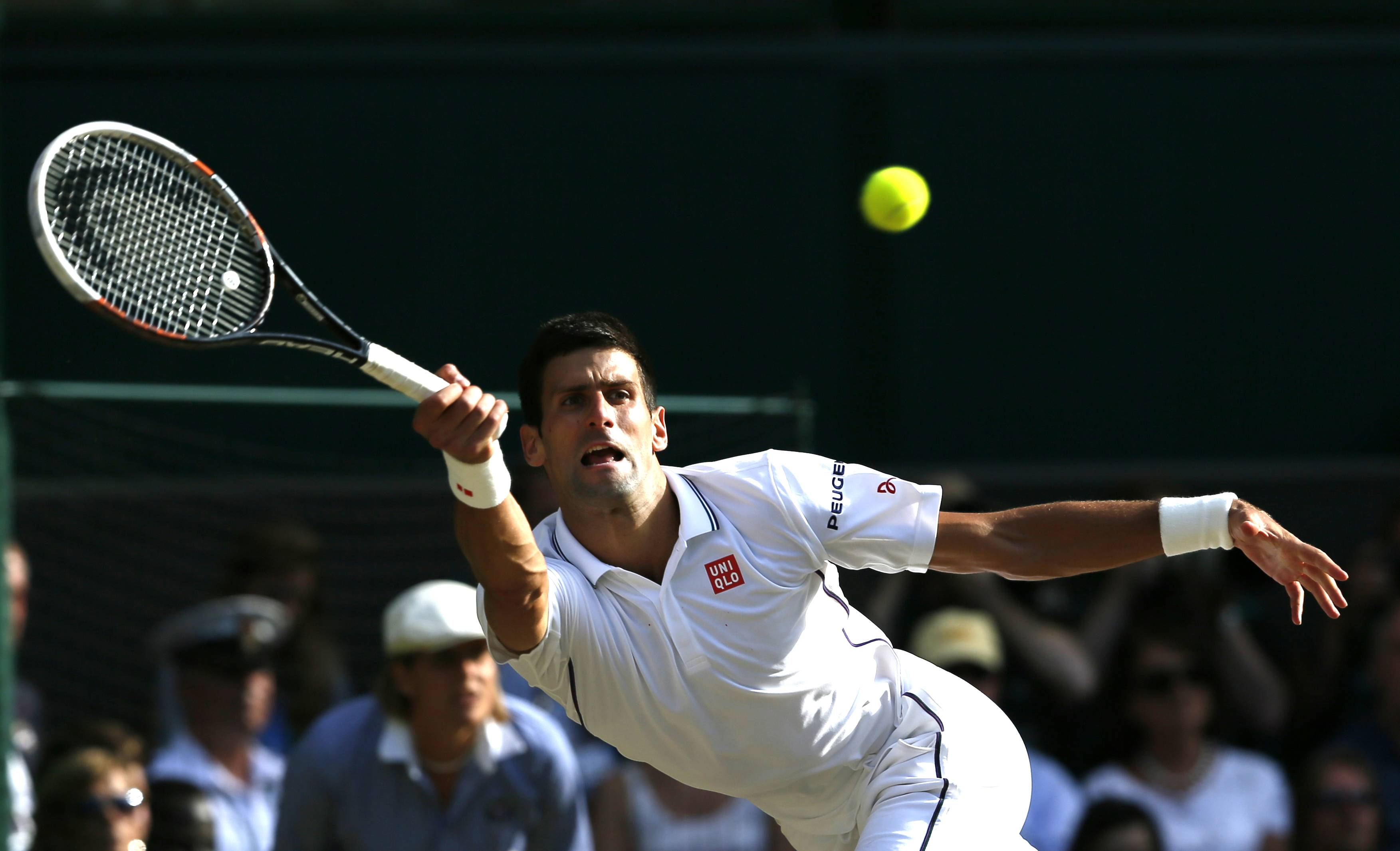 Novak Djokovic of Serbia plays a return to Roger Federer of Switzerland during their men's singles final at the All England Lawn Tennis Championships in Wimbledon, London, Sunday, July 6, 2014.