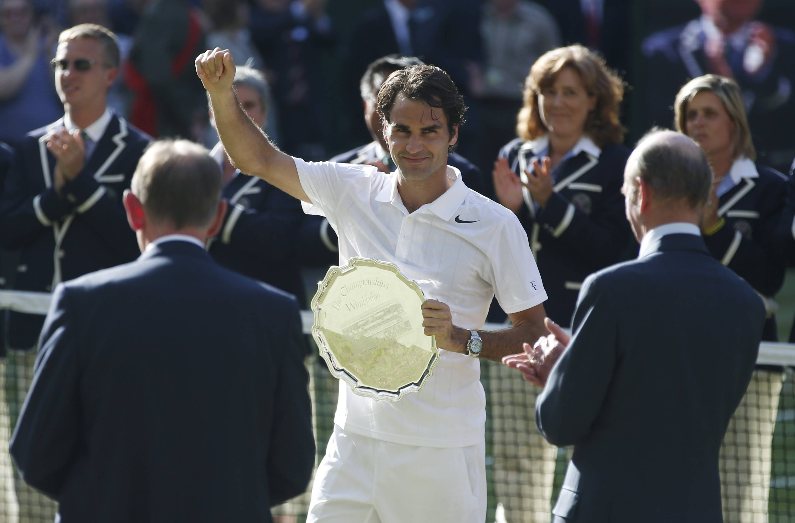Roger Federer of Switzerland holds the runner up trophy after being defeated by Serbia's Novak Djokovic in the men's singles final at the All England Lawn Tennis Championships in Wimbledon, London, Sunday July 6, 2014.