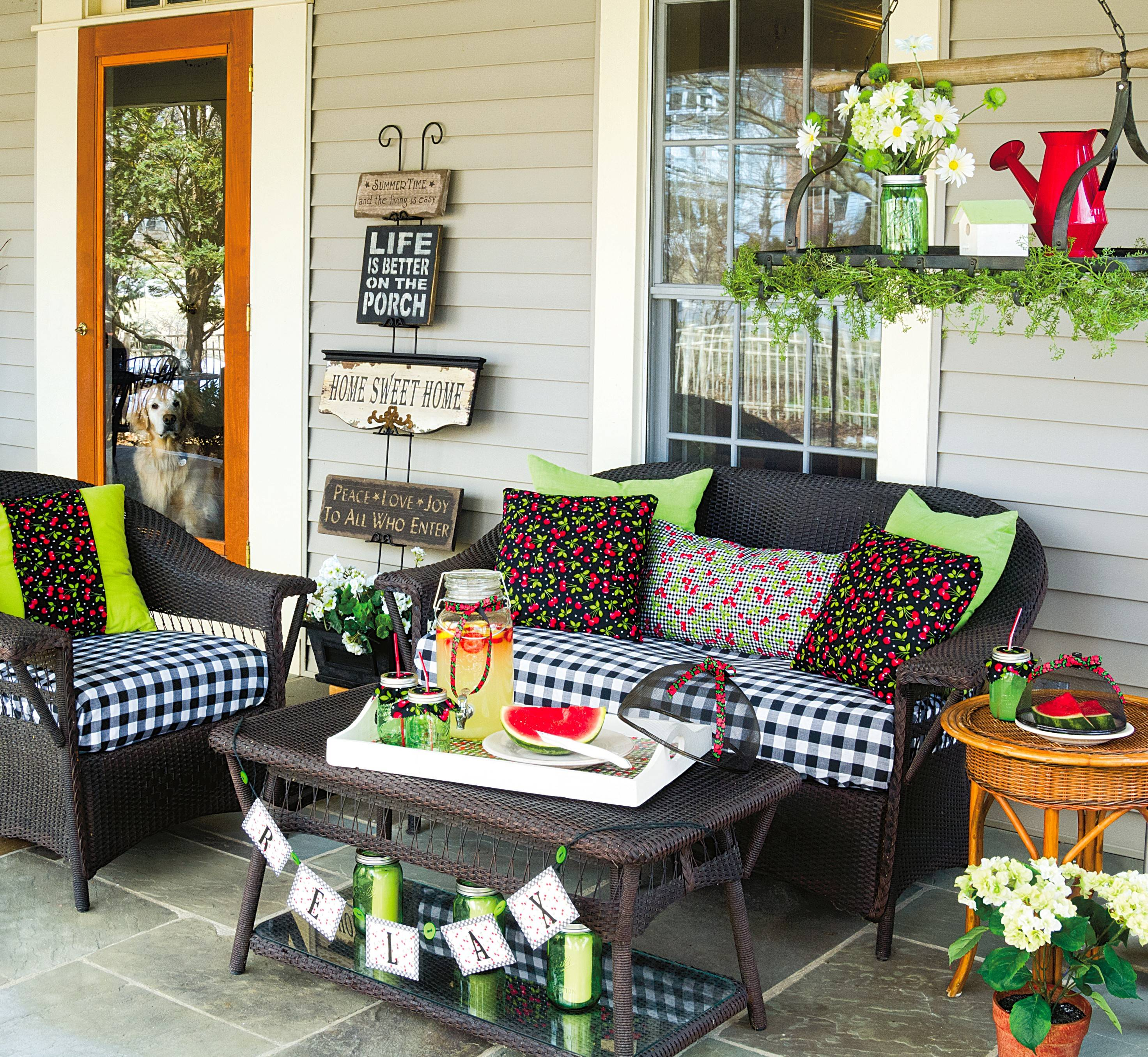 Create a recurring theme throughout your porch seating area by picking a summer icon and working it into your decor. Here, cheery cherry-covered pillows look perfect on the black-and-white checked cushions and infuse the area with their sweet style.