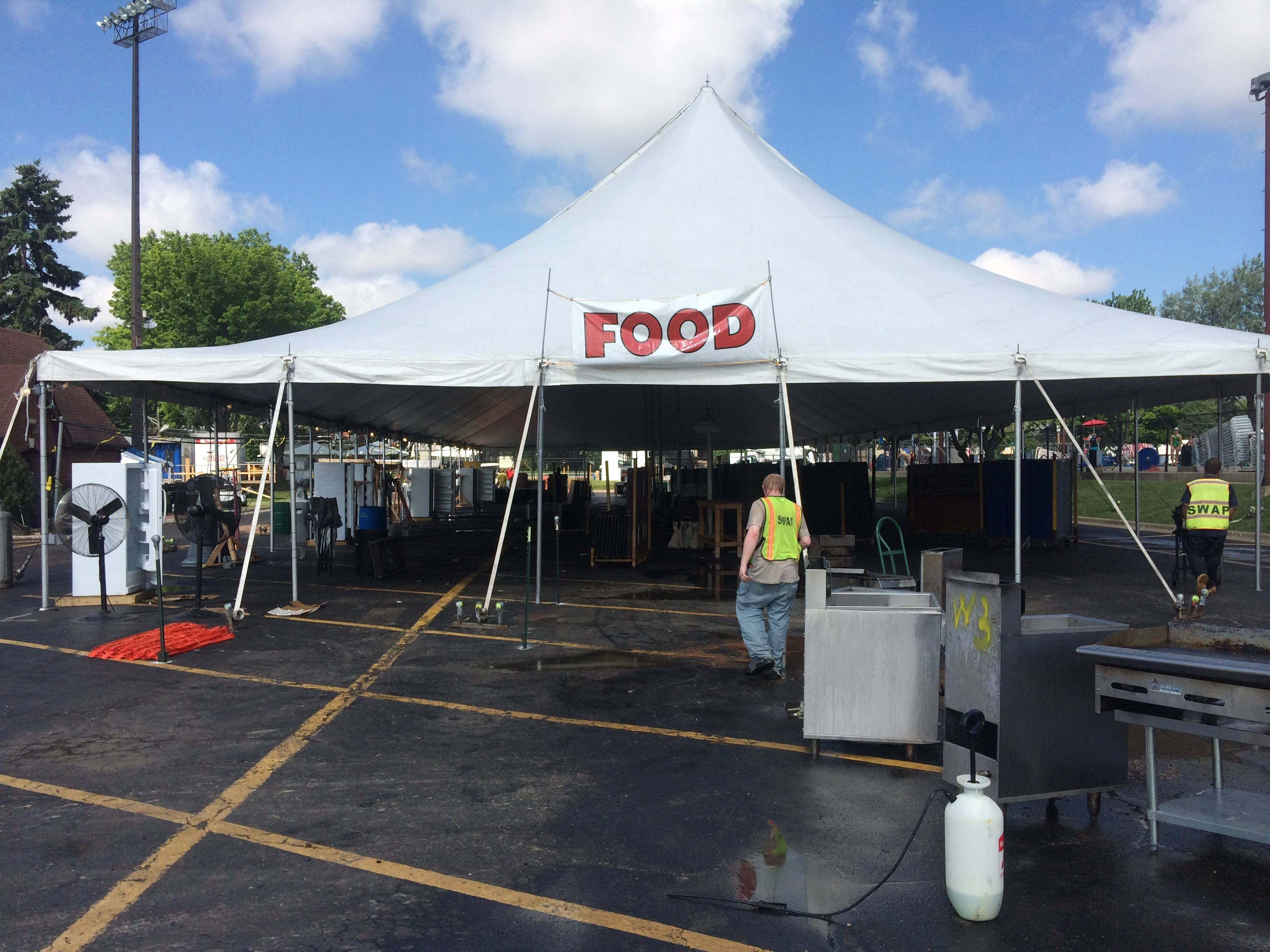A worker with the Cook County Sheriff's Work Alternative Program moves a grill Monday morning while cleaning up a Frontier Days tent in Arlington Heights. Boosted by good weather and big-name acts, organizers said this year's fest was a big success.