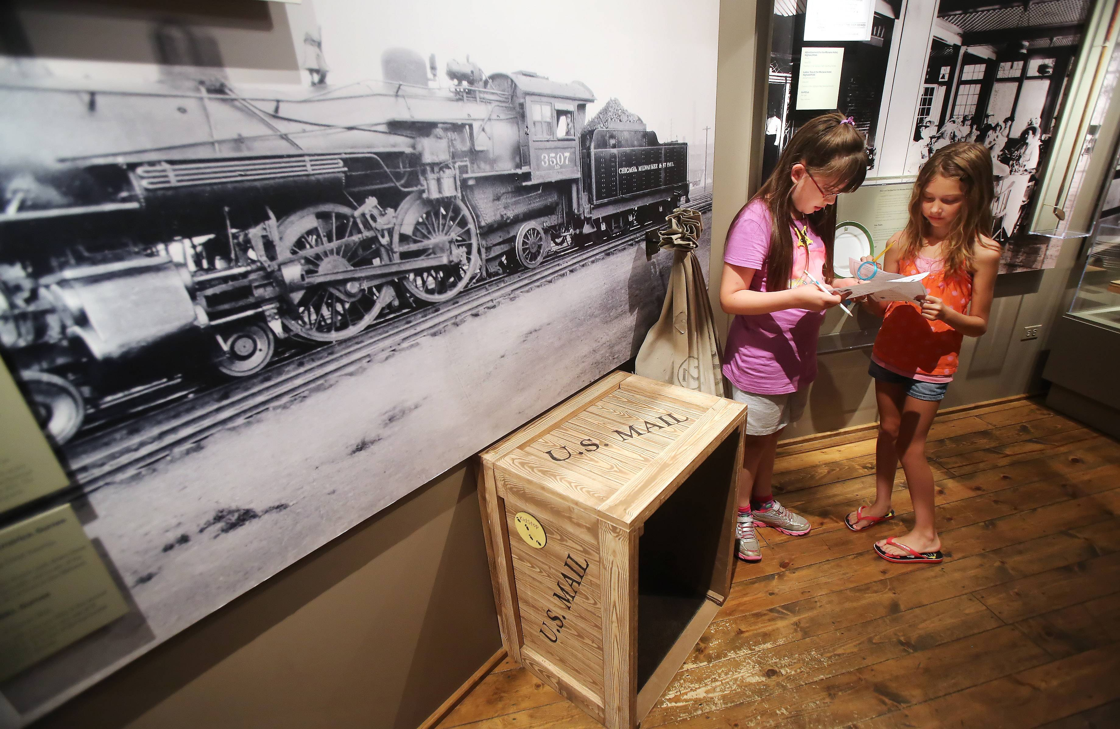 Ava McQuain, left, and Abby Ray, both 9 and from Mundelein, use their new detective skills Monday during a scavenger hunt at the Lake County Discovery Museum near Wauconda. Their mission, as part of the Lake County Forest Preserve District's History Detectives day camp, was to solve the biggest train robbery in county history, the 1924 Rondout Robbery.