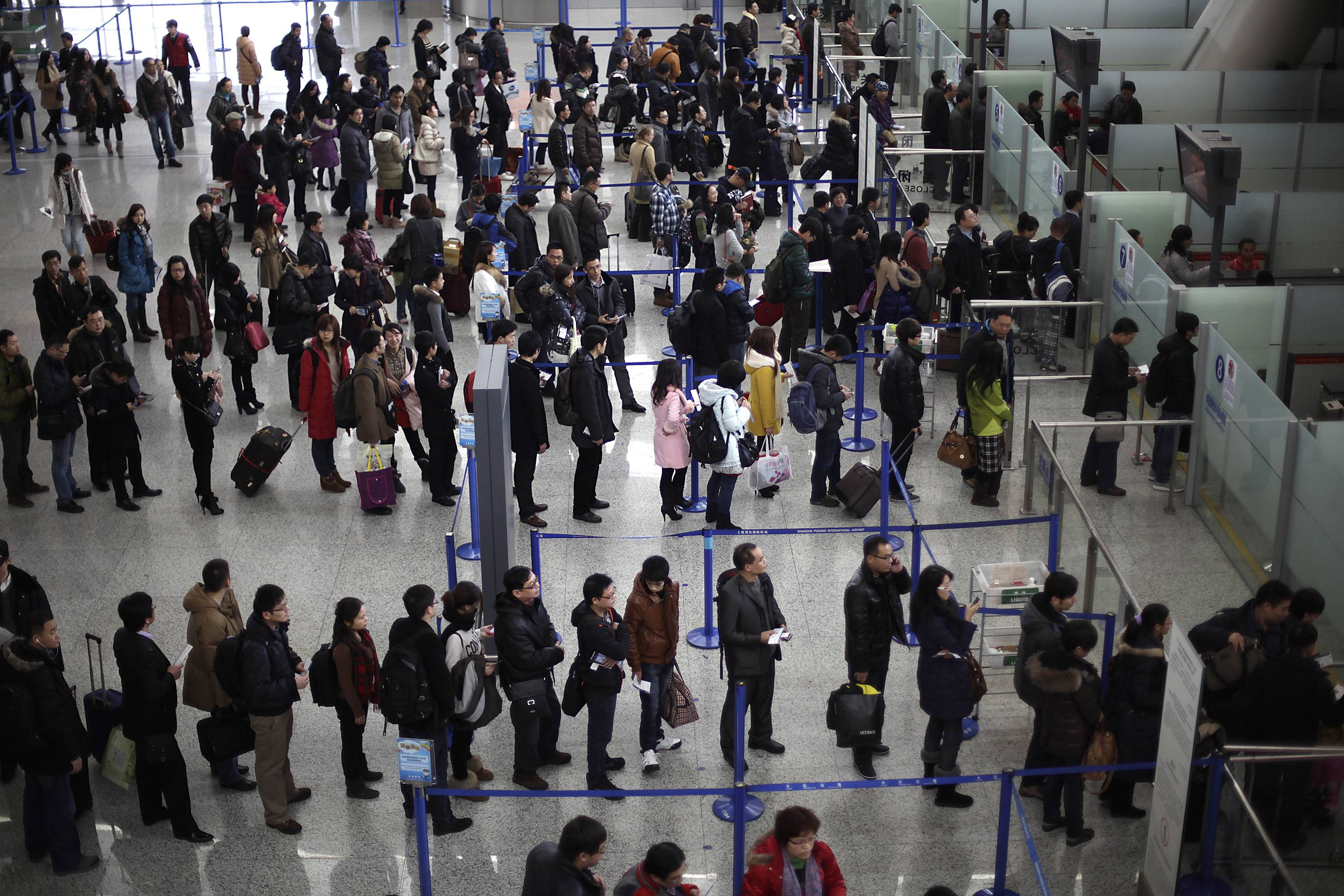 In 2012 photo, passengers queue up for a security check at Pudong International Airport in Shanghai, China. The Transportation Security Administration is requiring passengers at some overseas airports that offer U.S.-bound flights to power on their electronic devices.