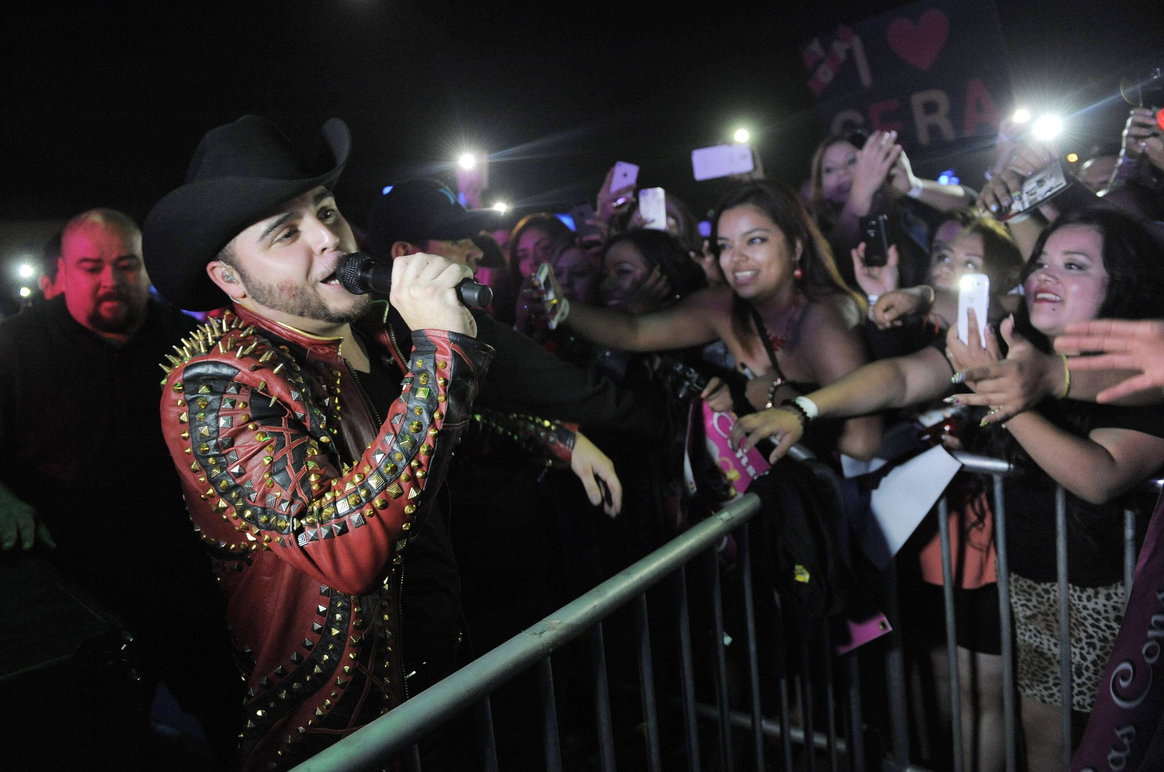 "Gerardo Ortiz performs in front of fans during a concert at the Ventura County Fairgrounds on in Ventura, Calif. Ortiz spent his childhood in the Pacific coast state of Sinaloa, the birthplace of both banda music and many of Mexico's top drug traffickers. But it was upon his return to Southern California that he found fame and fortune after self-promoting his ballads and ""narcocorridos"" on YouTube."
