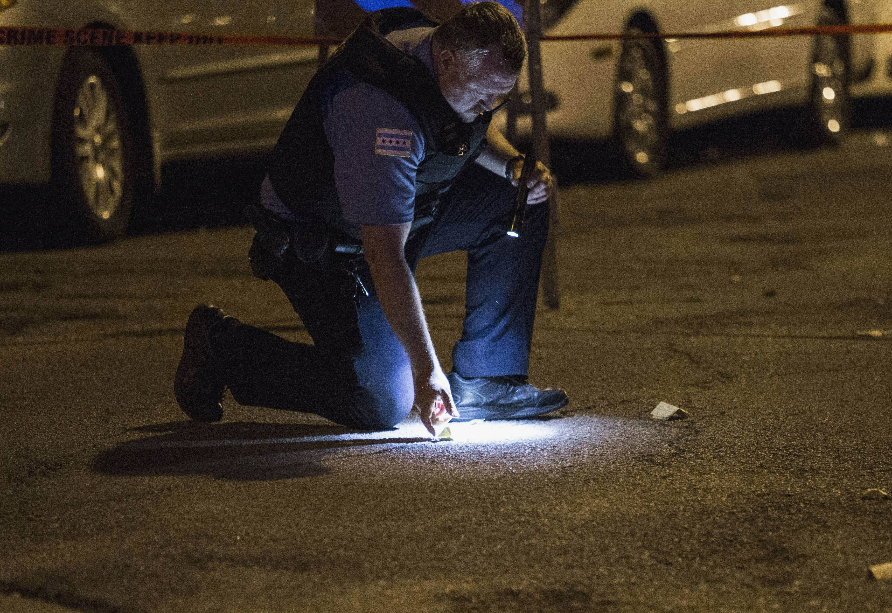 A Chicago police officer checks on evidence at the scene where a man was shot Sunday in Chicago's Uptown neighborhood. The Fourth of July weekend was a bloody one in Chicago, where at least nine people were shot to death and at least 60 others were wounded.