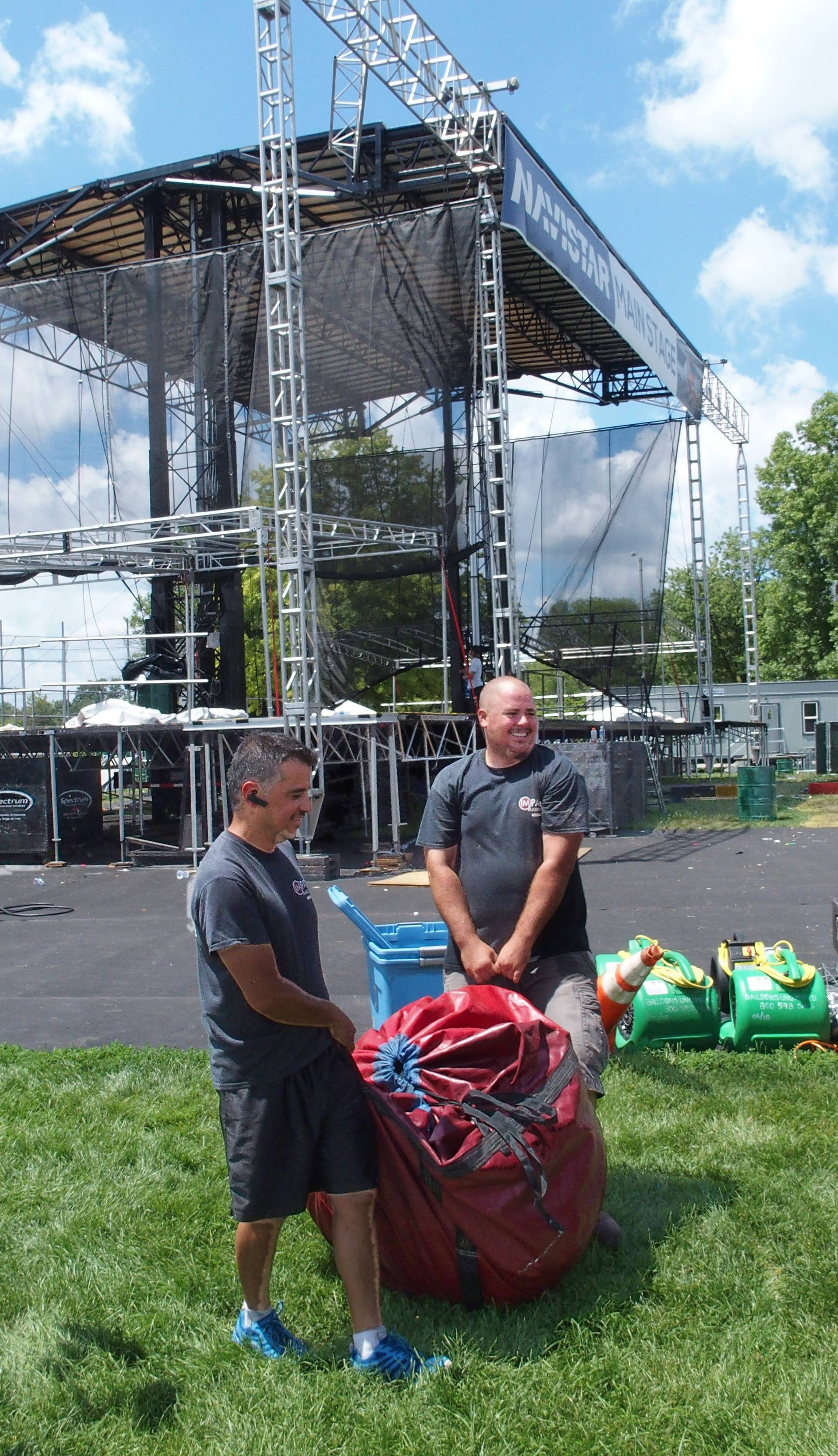 William Carrerro and Paul Mitchell haul away a bag containing a large advertising balloon that had been displayed near the main stage of Ribfest in Naperville. Cleanup of the park is set to conclude Tuesday after the four-day festival.