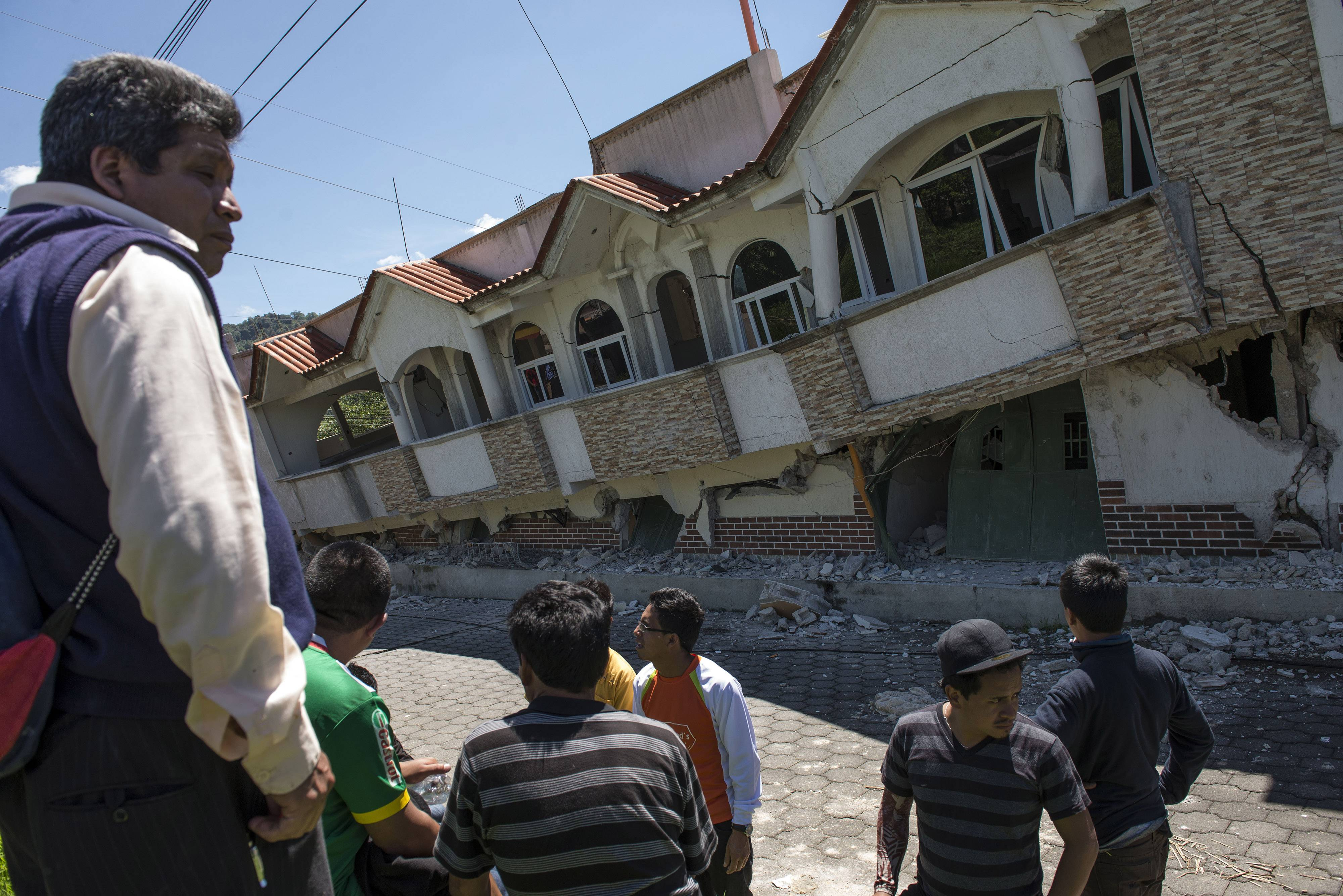 Neighbors gather outside homes that collapsed during an earthquake in San Pedro, Guatemala, Monday. A magnitude-6.9 earthquake on the Pacific Coast jolted a wide area of southern Mexico and Central America Monday.