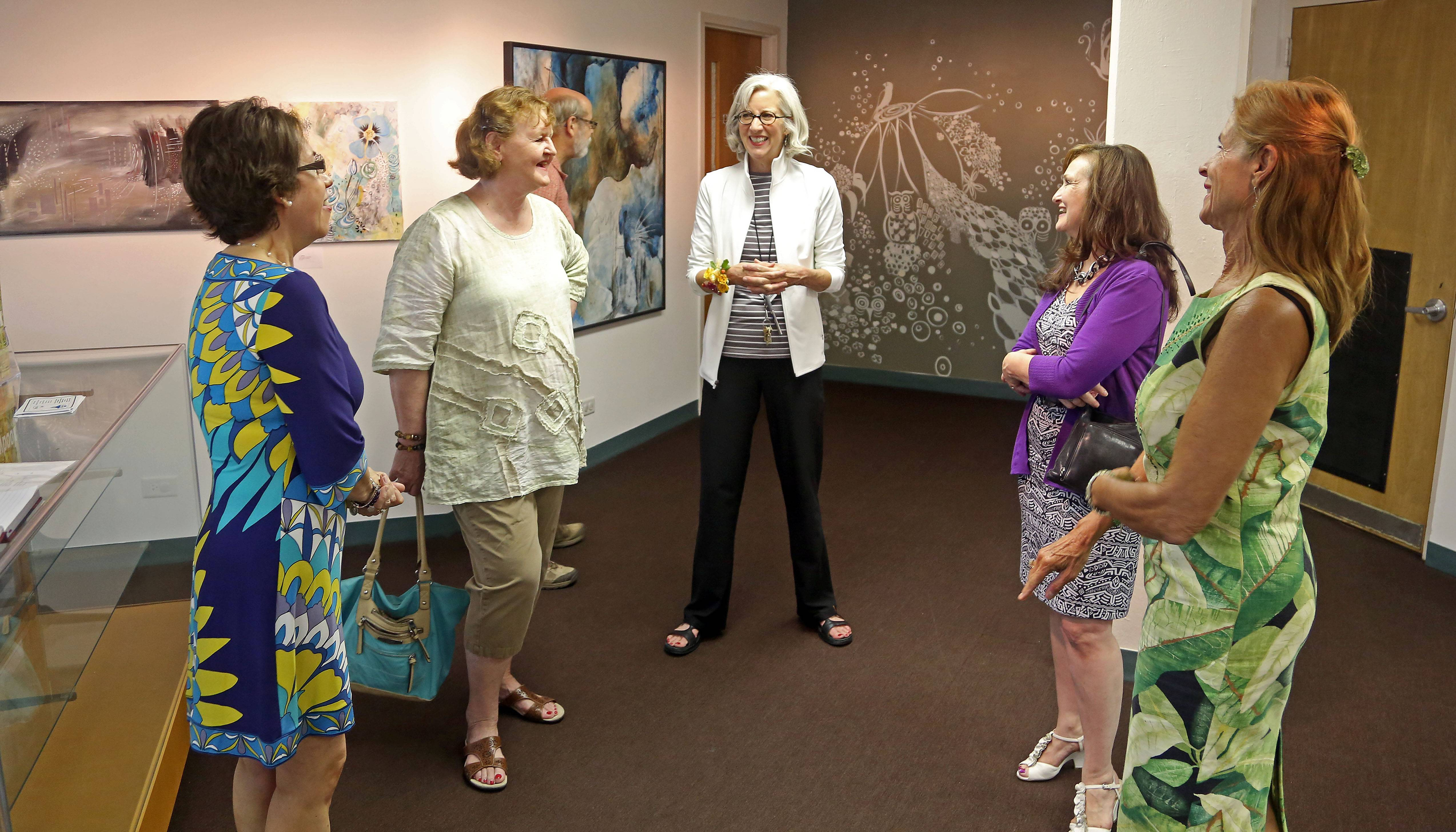 Susan Matthews, middle, talks with people attending a gallery opening in June for Roselle artist Paulina Engel at the Hanover Park Park District gallery. Matthews has retired from her job as cultural arts director for the Hanover Park Park District. The gallery is being renamed after Matthews.