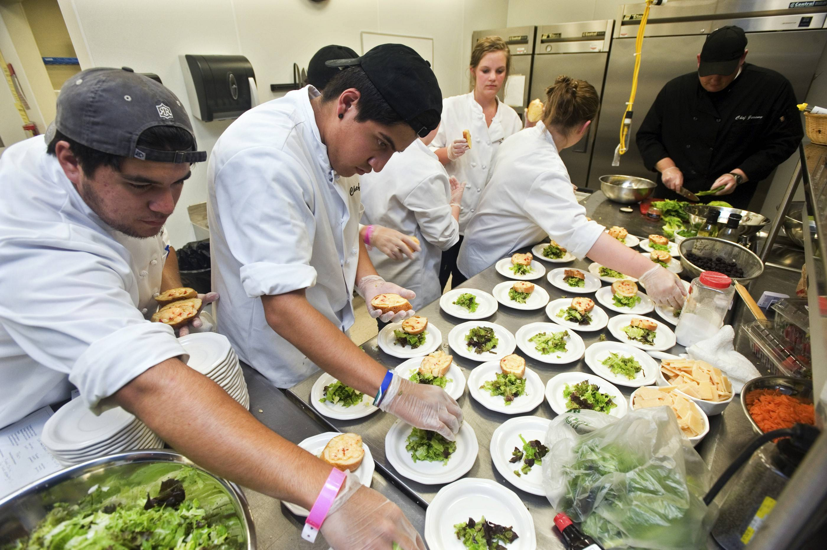 Students work on preparing bruschetta during a culinary camp at Eastern Illinois University in Charleston. Jeremy Ryan, right, is assisting EIU's Apprentice Chef Cooking School as head chef during the program.