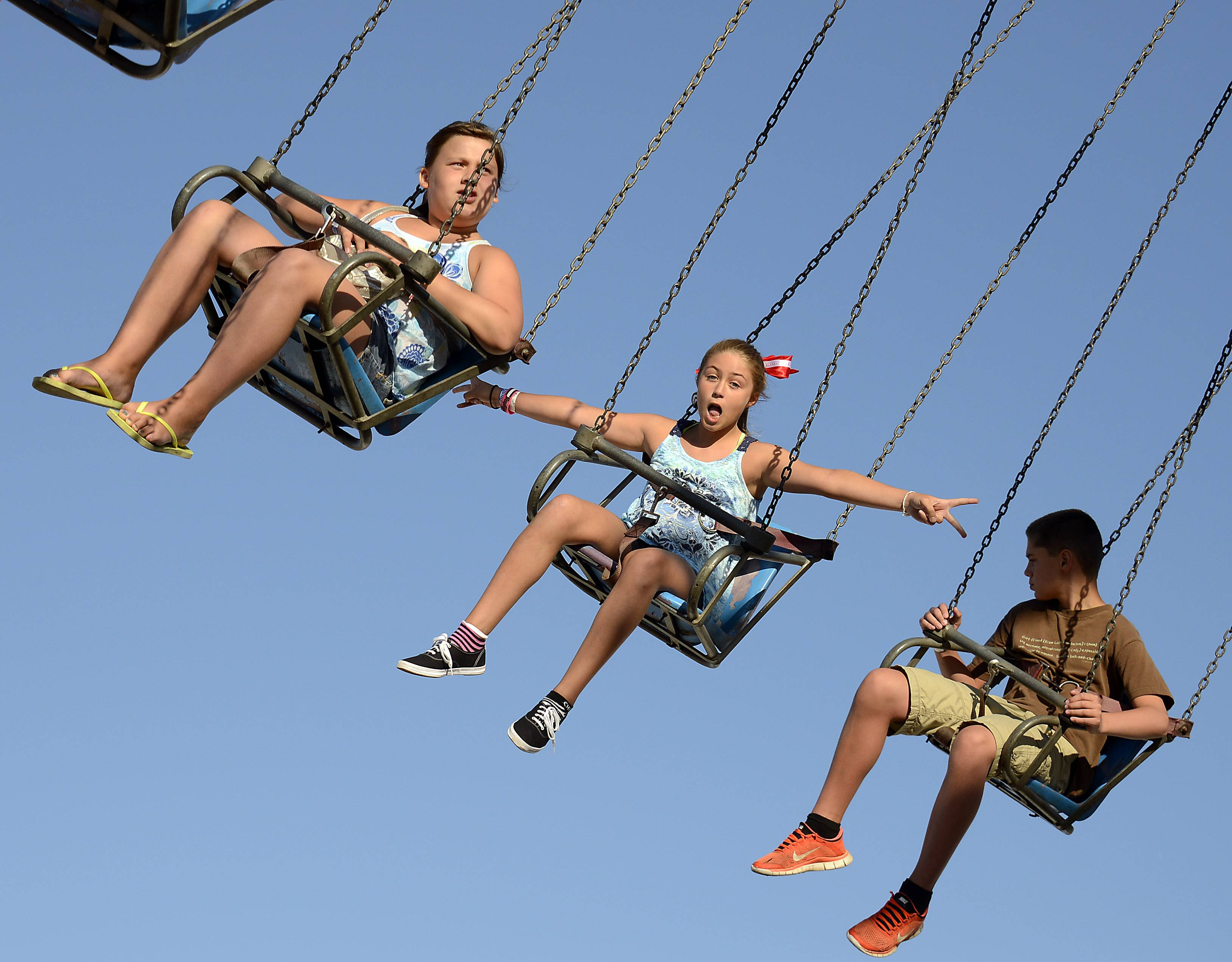 Lainey Sporrer, 10, of Hoffman Estates, middle, flies high on the Yo Yo with her friends at the Northwest Fourth Fest in Hoffman Estates on Thursday.