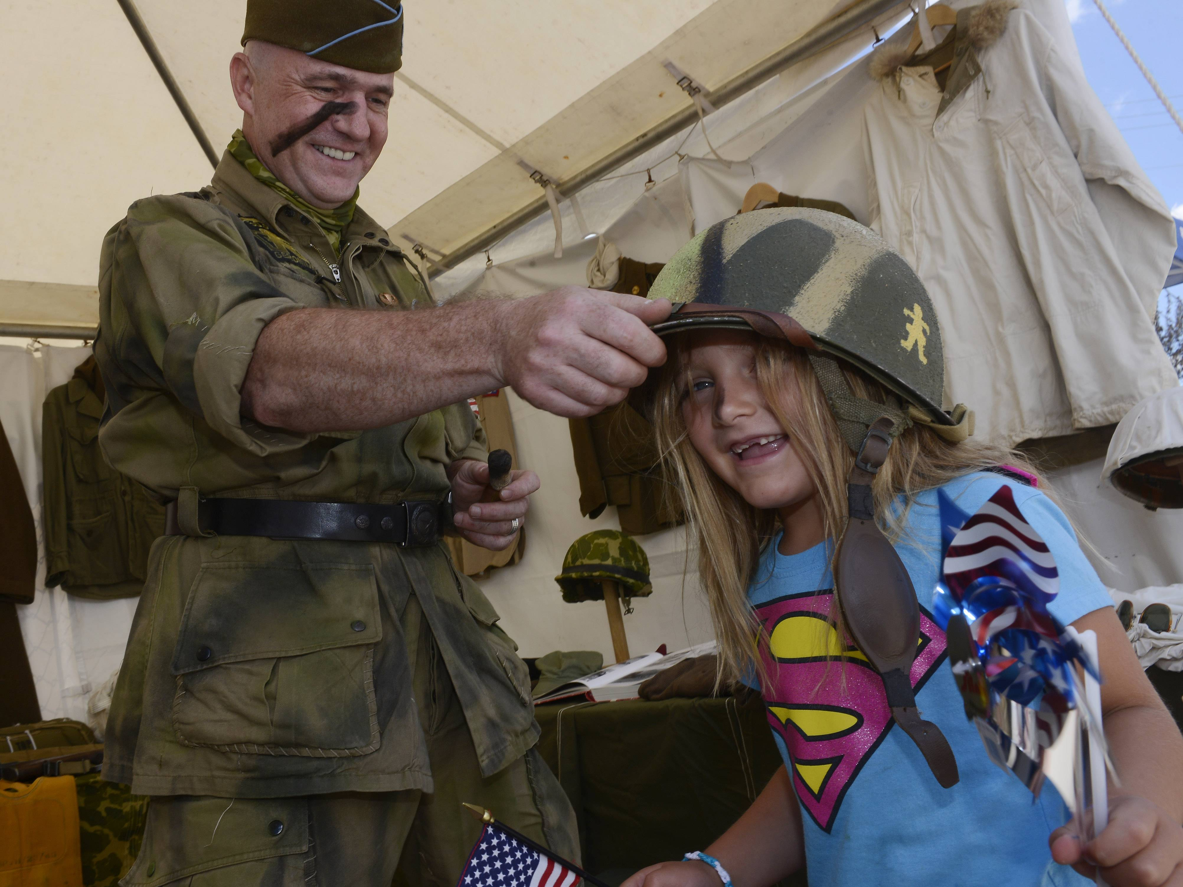 Chloe Mosele, 5, of Barrington, tries on an army helmet with the assistance of Stephane Goupil while visiting the 509th Parachute Infantry Battalion display during Thursday's festival in Barrington.