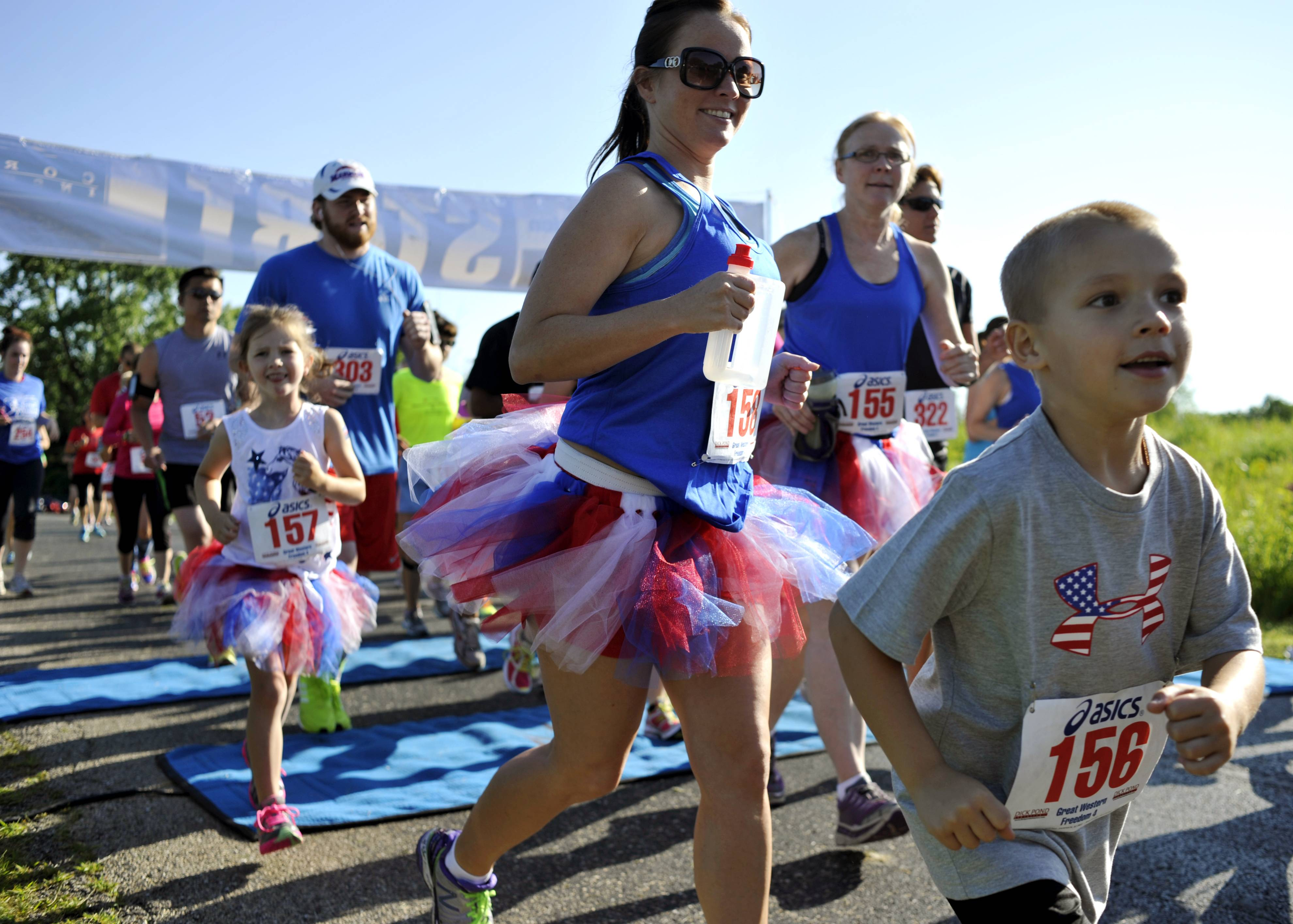 Aiden Jaquez, 6, gets a head start with his family, Margie Clark, Addison Clark, 6, and grandmother Kathleen Taylor, of Montgomery, close behind him at the July Fourth Great Western Freedom 4 to benefit Lazarus House at the LeRoy Oakes Forest Preserve in St. Charles on Friday.