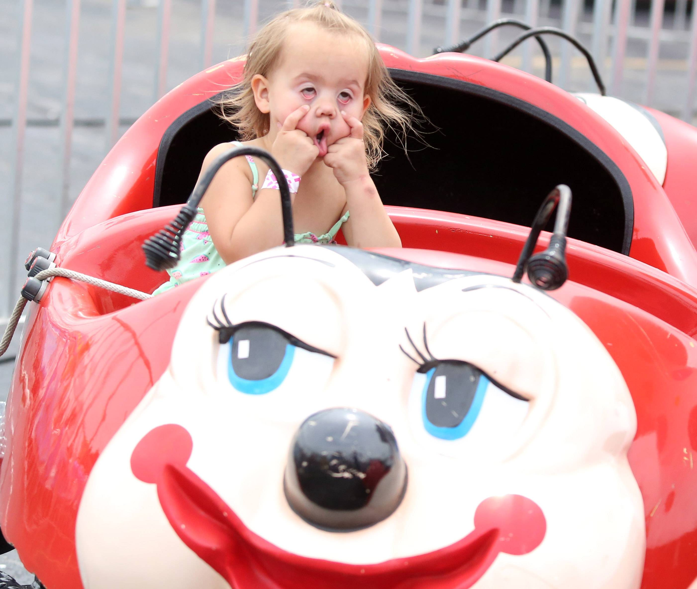 Paige Swarthout, 3, of Carpentersville, makes faces at her parents as she rides the Ladybug at Northwest Fourth-Fest on Saturday in Hoffman Estates.