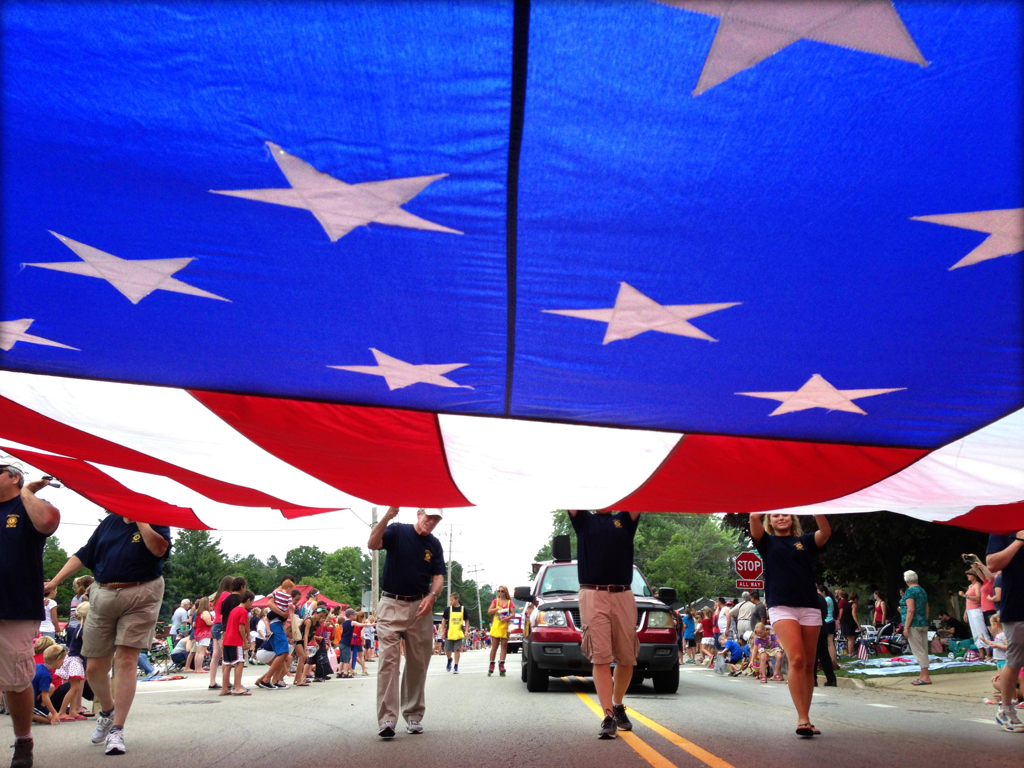 Lions Club members carry a large American flag during the Crystal Lake Fourth of July parade on Dole Avenue Sunday afternoon.