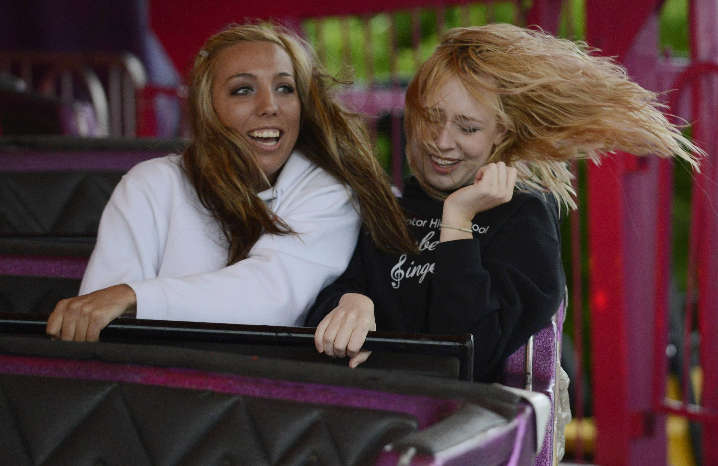 "Kailey Leahy, left, of Inverness, and Jackie Jensen of Arlington Heights hang on as they spin backward on the ""Matterhorn"" during opening night of Frontier Days in Arlington Heights Wednesday."