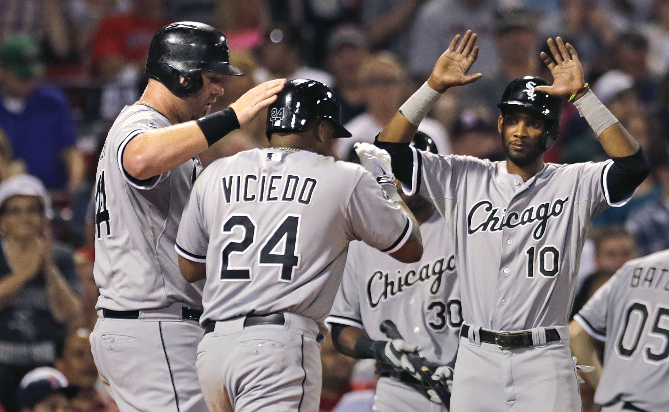 White Sox' Dayan Viciedo (24) is congratulated by teammates Adam Dunn, left, and Alexei Ramirez (10) after his three-run, home run off Boston Red Sox starting pitcher Clay Buchholz during the fourth inning of a baseball game at Fenway Park in Boston, Monday, July 7, 2014.