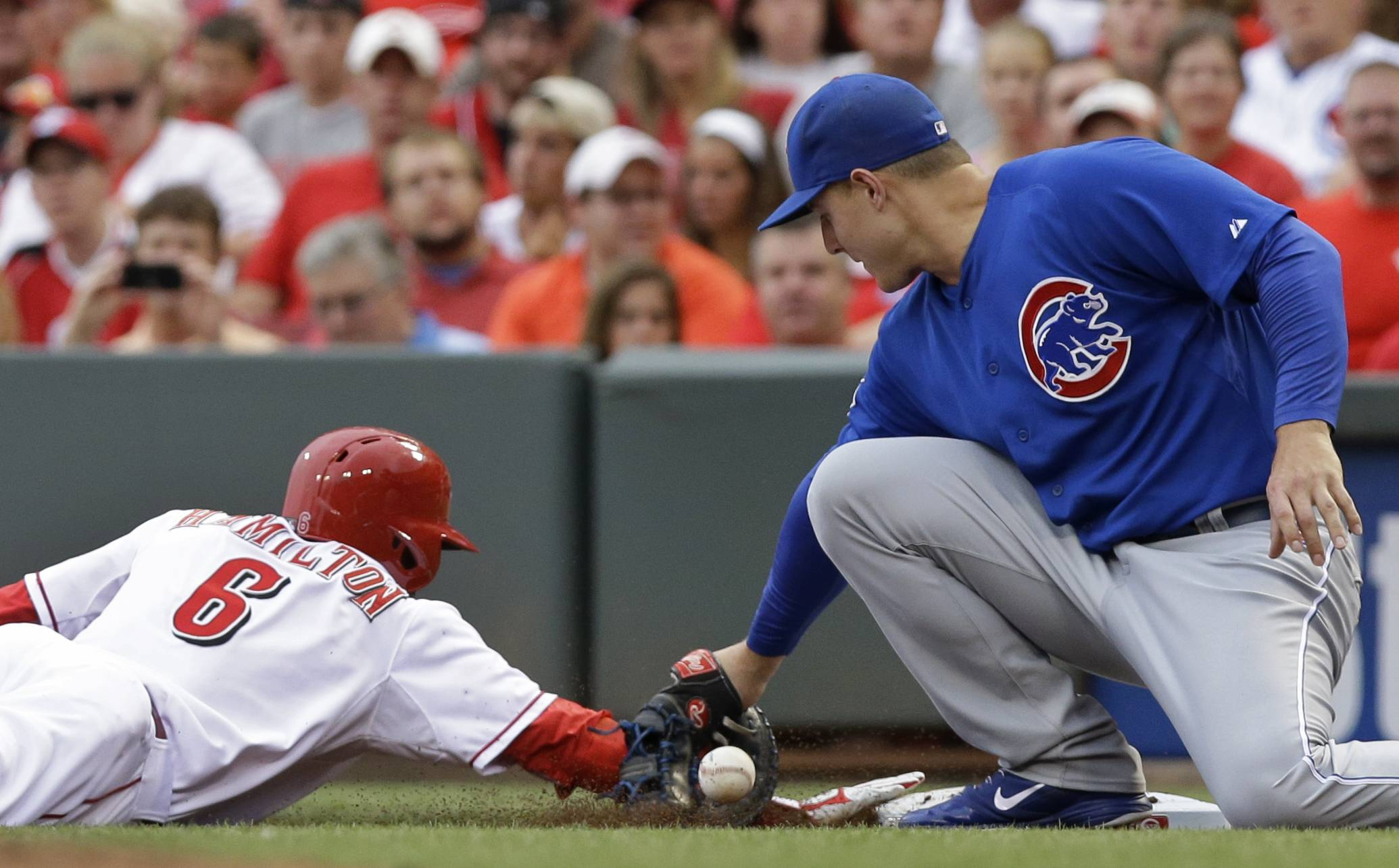 Cincinnati Reds' Billy Hamilton (6) dives safely back to first base as Chicago Cubs first baseman Anthony Rizzo drops a pickoff throw from starting pitcher Edwin Jackson in the first inning of a baseball game, Monday, July 7, 2014, in Cincinnati.