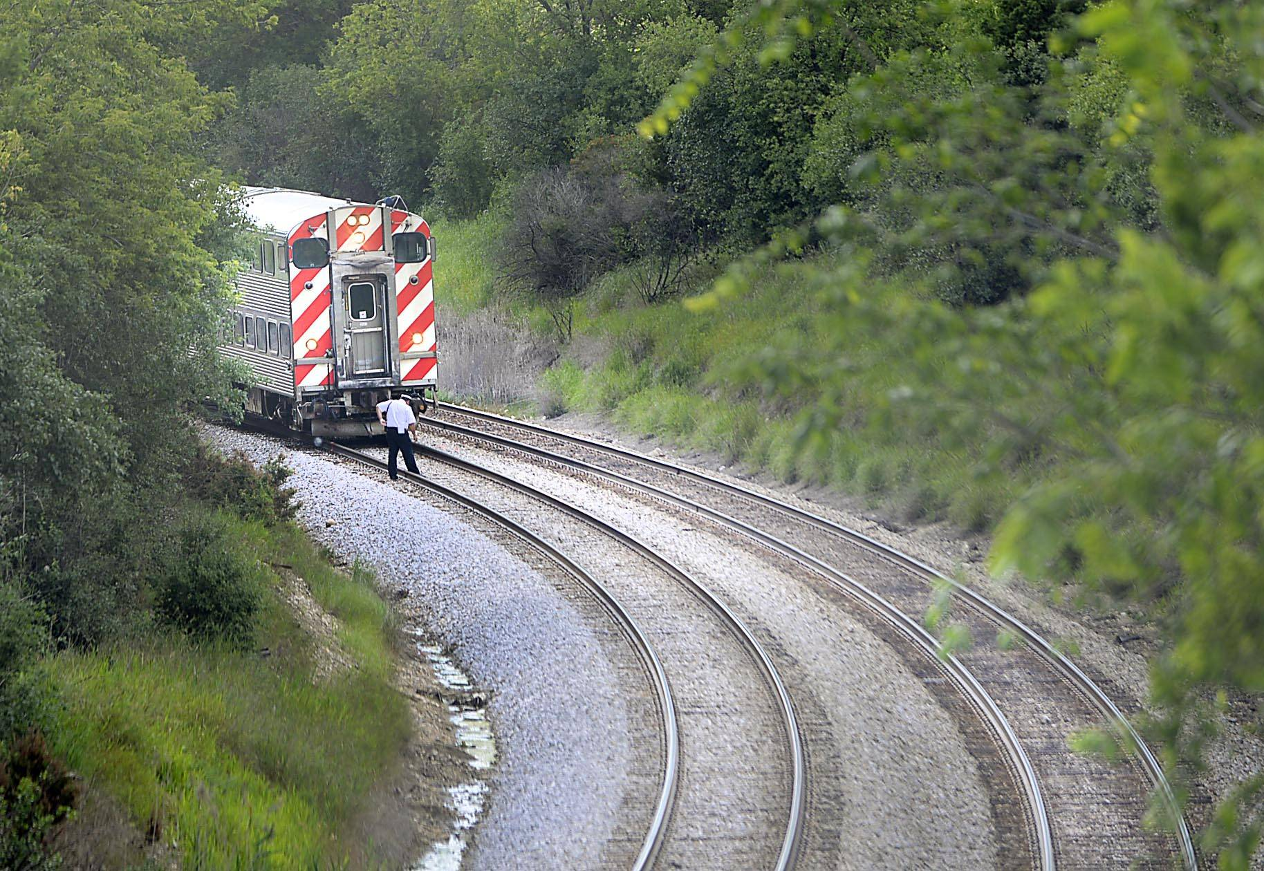 A man walks near a Metra train stopped on the tracks just west of Route 31 in Elgin Tuesday afternoon. A Metra spokesman said a Milwaukee District West Line train struck and killed a pedestrian shortly after leaving the Big Timber Road station.