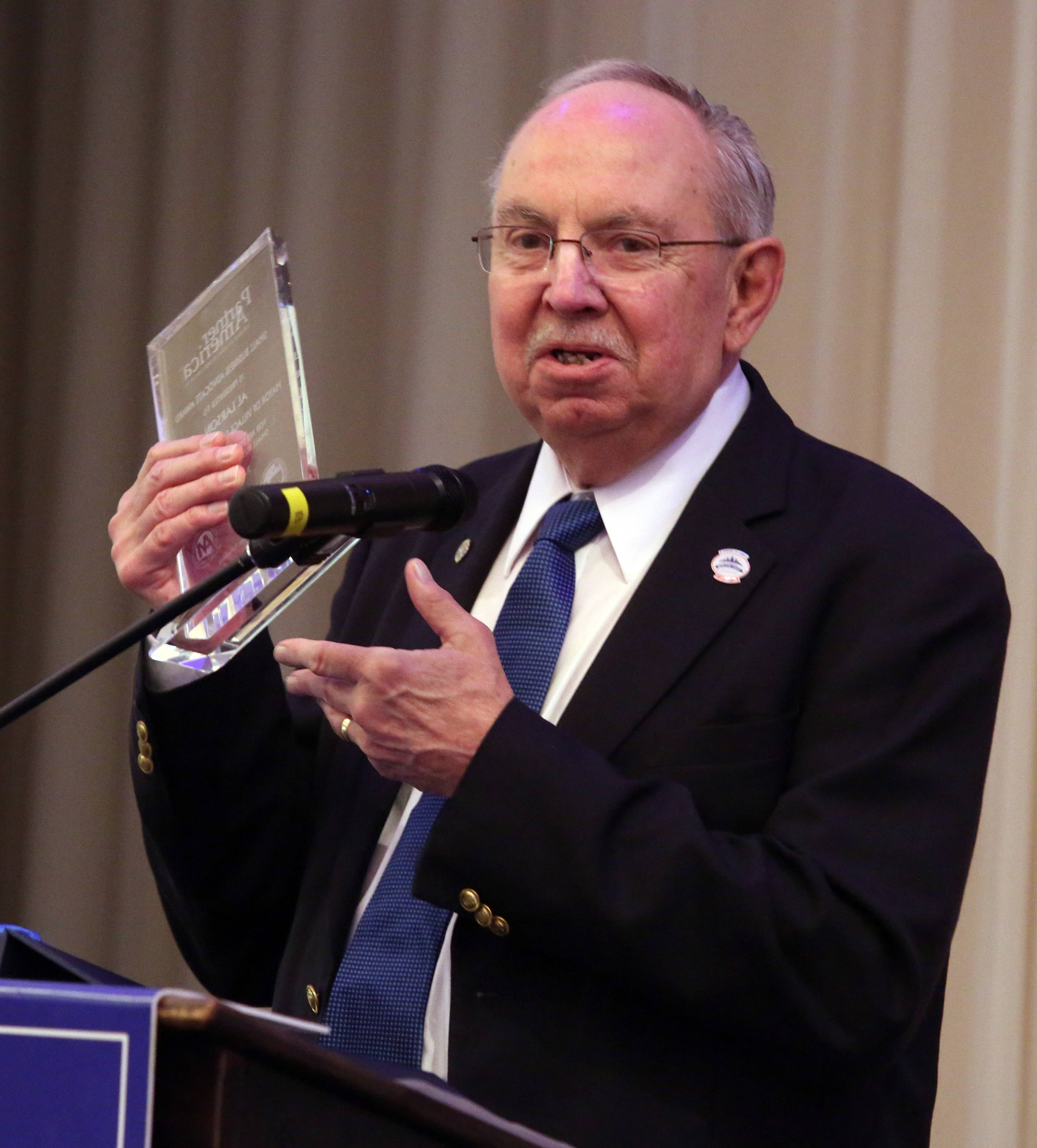 Schaumburg Mayor Al Larson holds up the U.S. Conference of Mayors Partner America Small Business Advocate Award he received Tuesday at the Schaumburg Business Association's monthly breakfast meeting. The award honors Larson's efforts to help small businesses grow in Schaumburg.