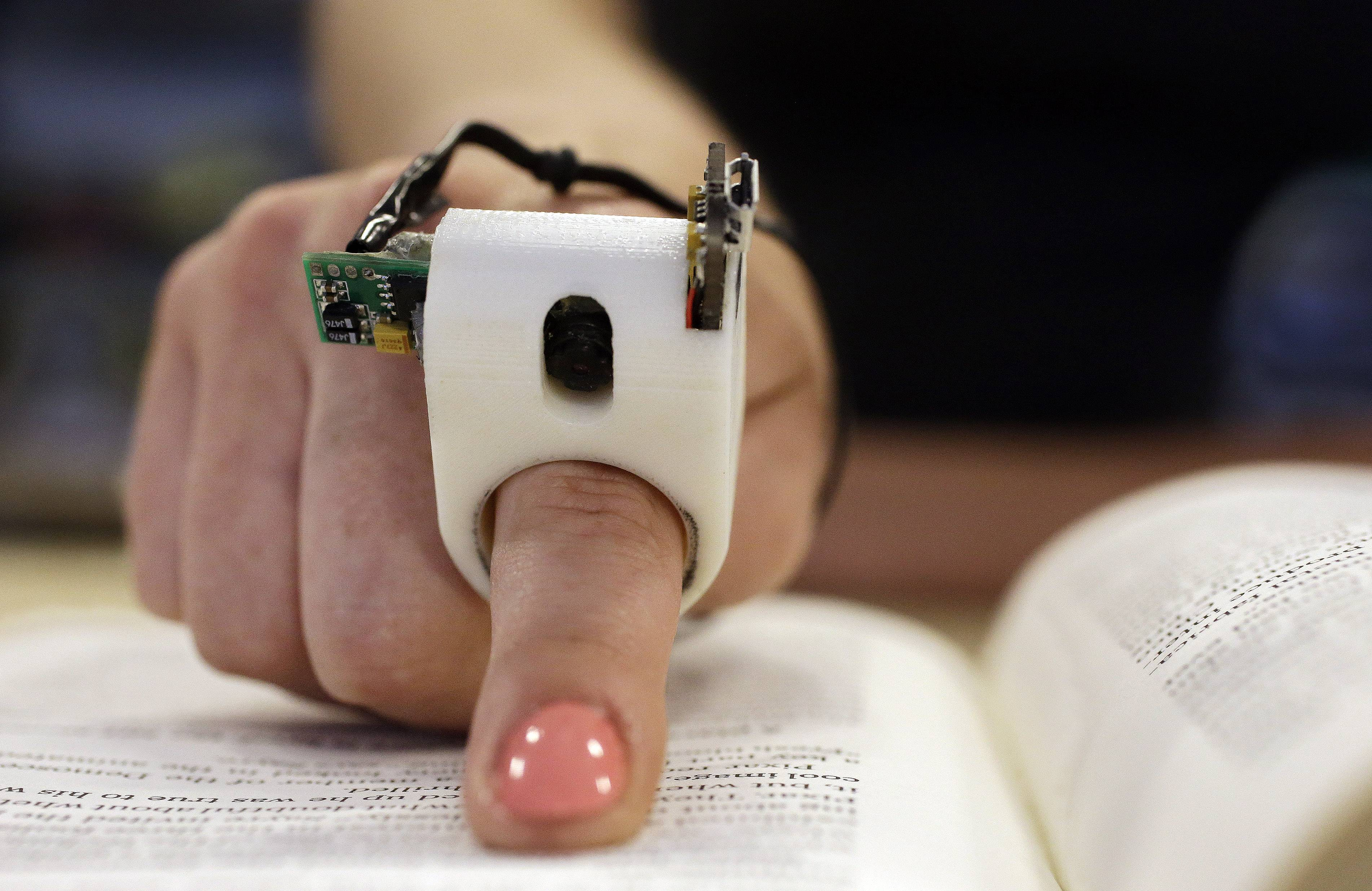 A model wears a FingerReader ring at the Massachusetts Institute of Technology's Media Lab in Cambridge, Mass. Researchers designed and developed the instrument, which enables people with visual disabilities to read text printed on paper or electronic devices.
