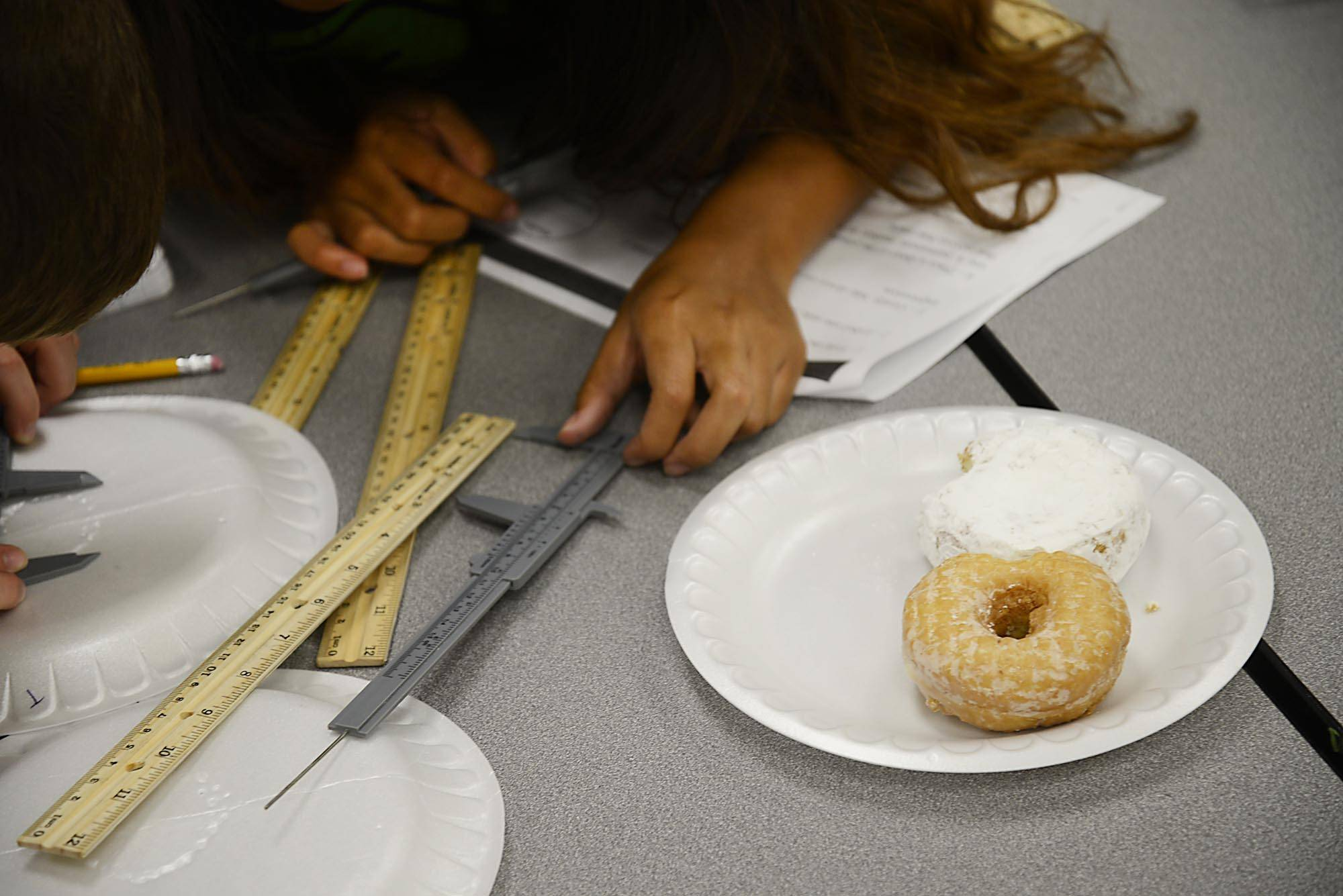 Students measure bite marks of suspects Wednesday in the case of the missing doughnuts in the CSI class of the McHenry County College summer Tech Camp in Crystal Lake.
